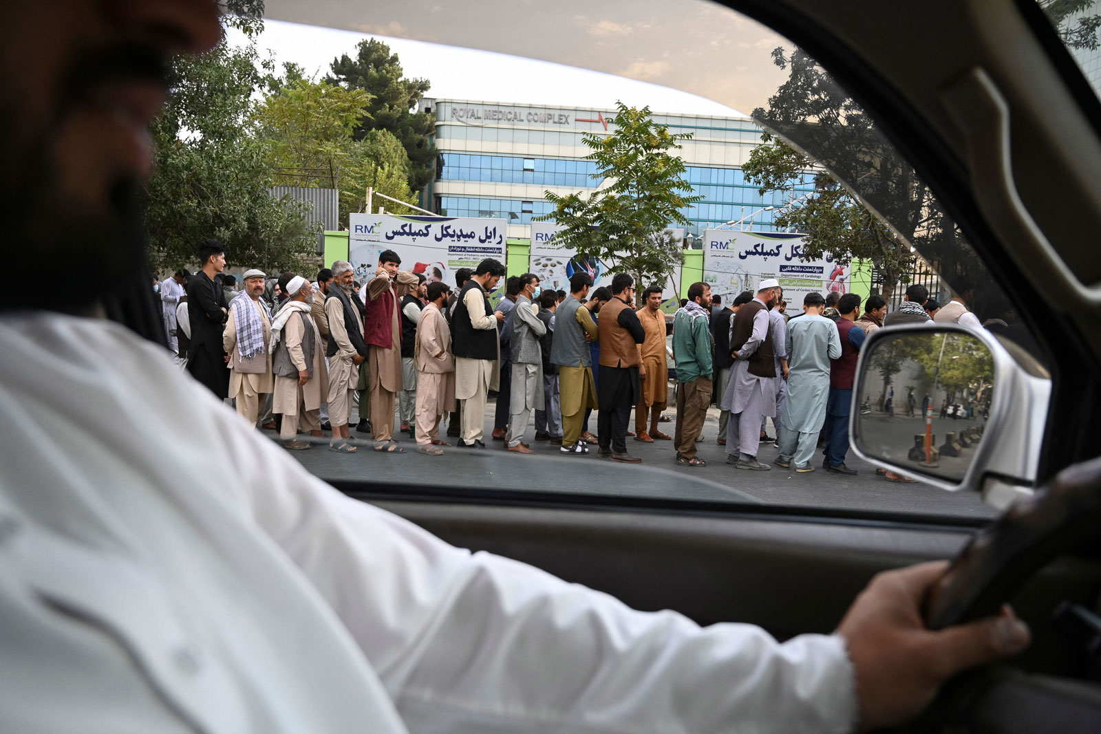 Afghans queue up as they wait for the banks to open in Kabul on August 31.