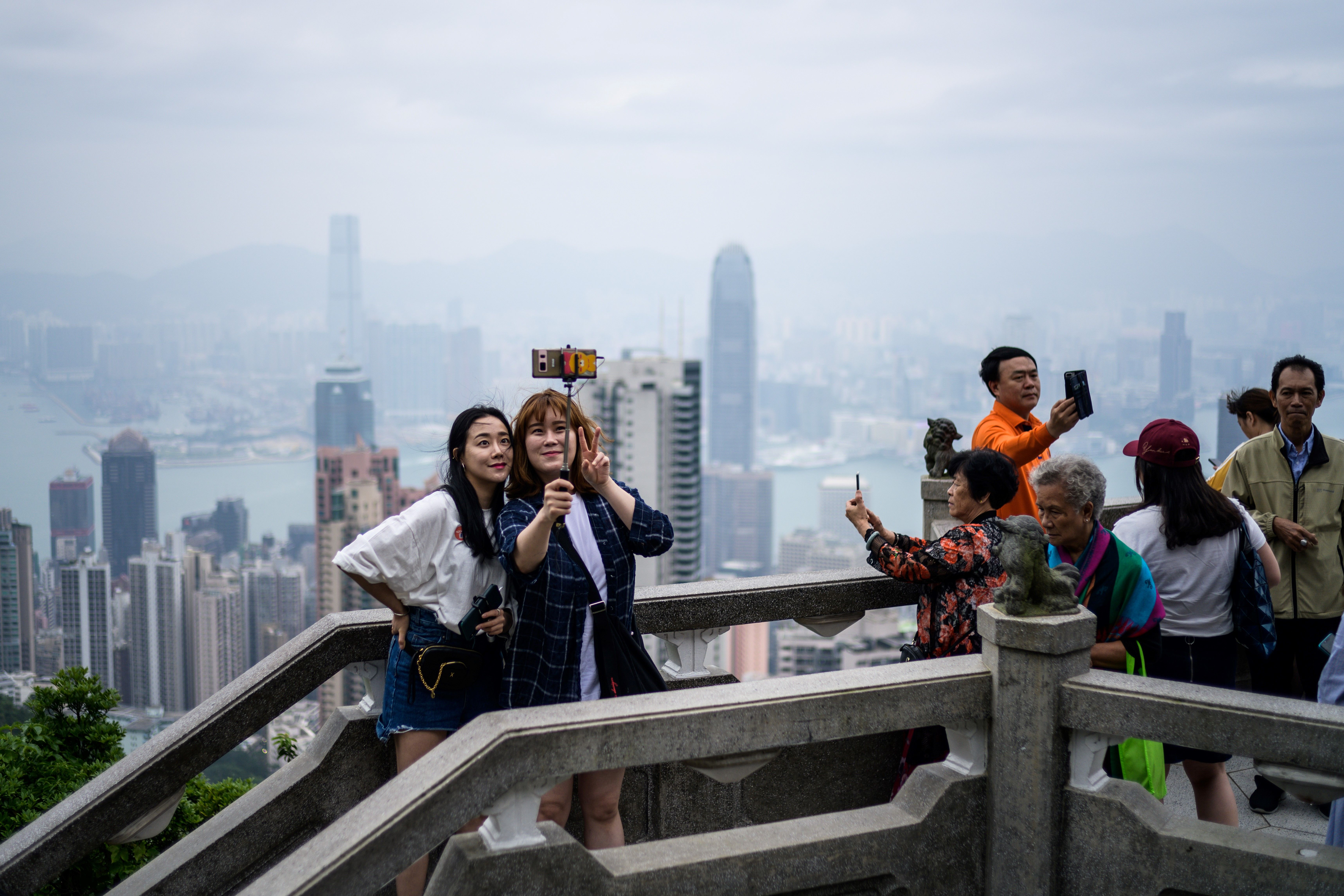 Tourists take selfies from Victoria Peak in front of a view of residential and commercial buildings in Kowloon (background) and Hong Kong Island on May 3.