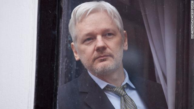 File photograph of Assange peering through the balcony window of the Ecuadorian embassy in central London on February 5, 2016.
