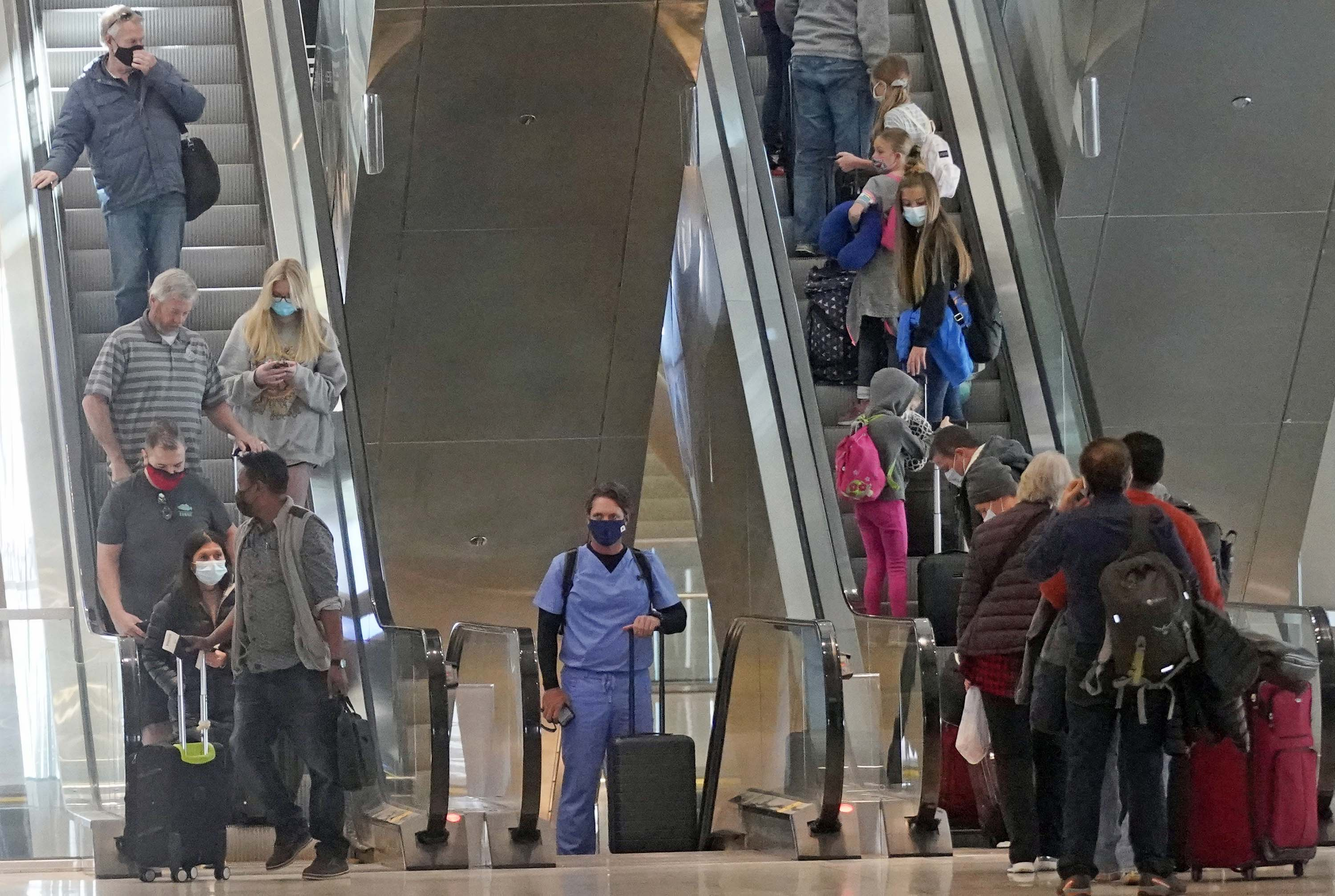 Travelers are seen at Salt Lake City International Airport in Utah, on Wednesday, March 17.