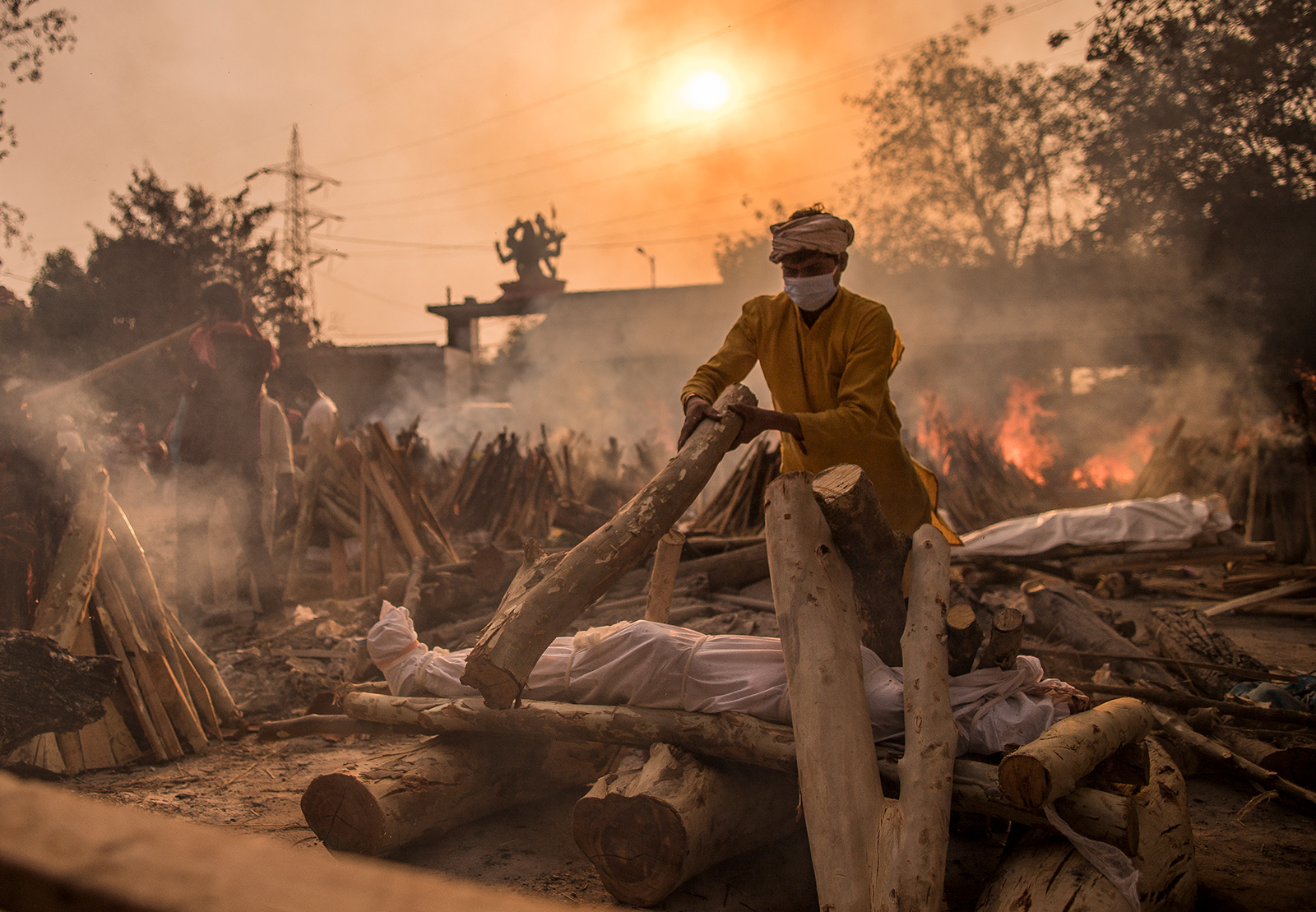 A priest performs the last rites of a patient who died of Covid-19 amid burning funeral pyres on May 1, in New Delhi, India.