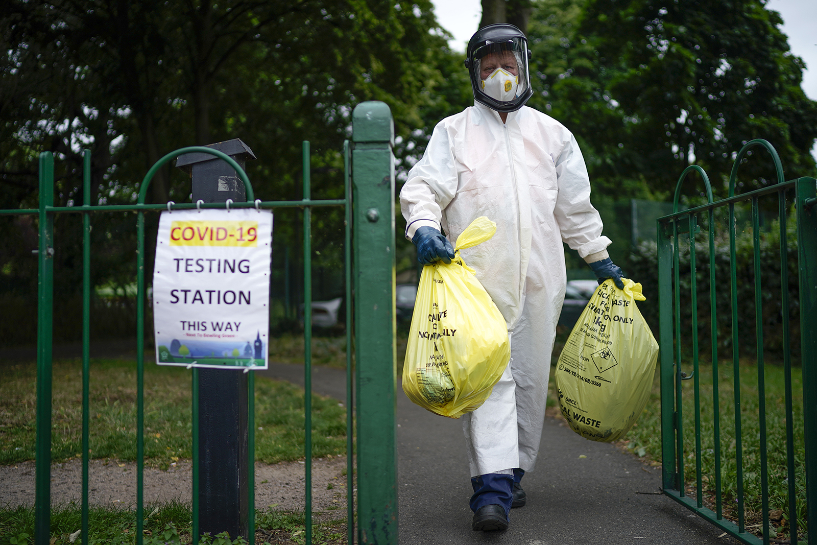 A city council worker carries rubbish from a coronavirus testing centre at Spinney Park on June 29, 2020 in Leicester, England.