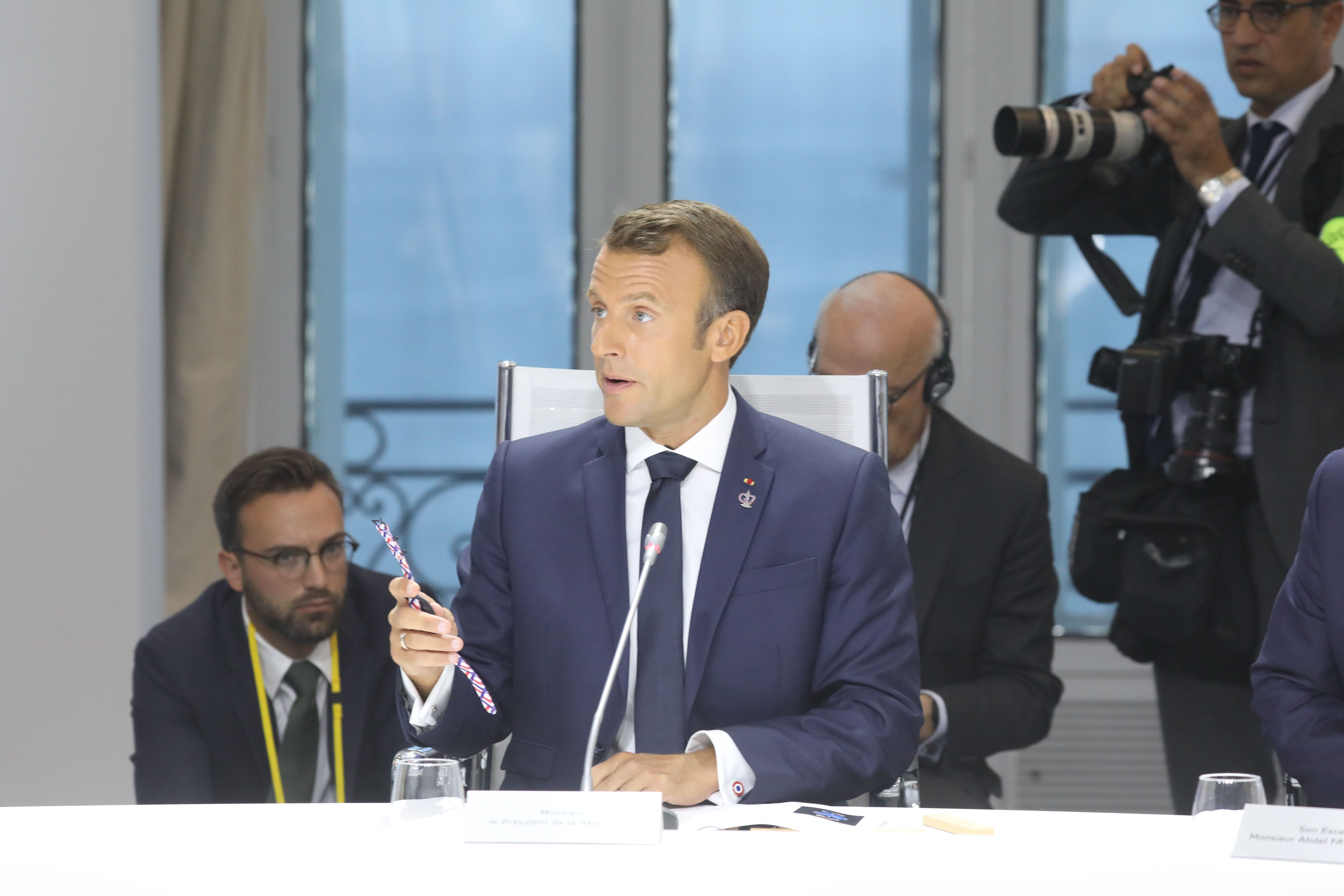 Macron shows off the watch made from recycled plastic.