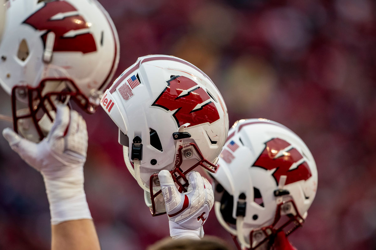 The Wisconsin Badgers raise their helmets prior to kickoff on November 24th, 2018 at the Camp Randall Stadium in Madison, WI.
