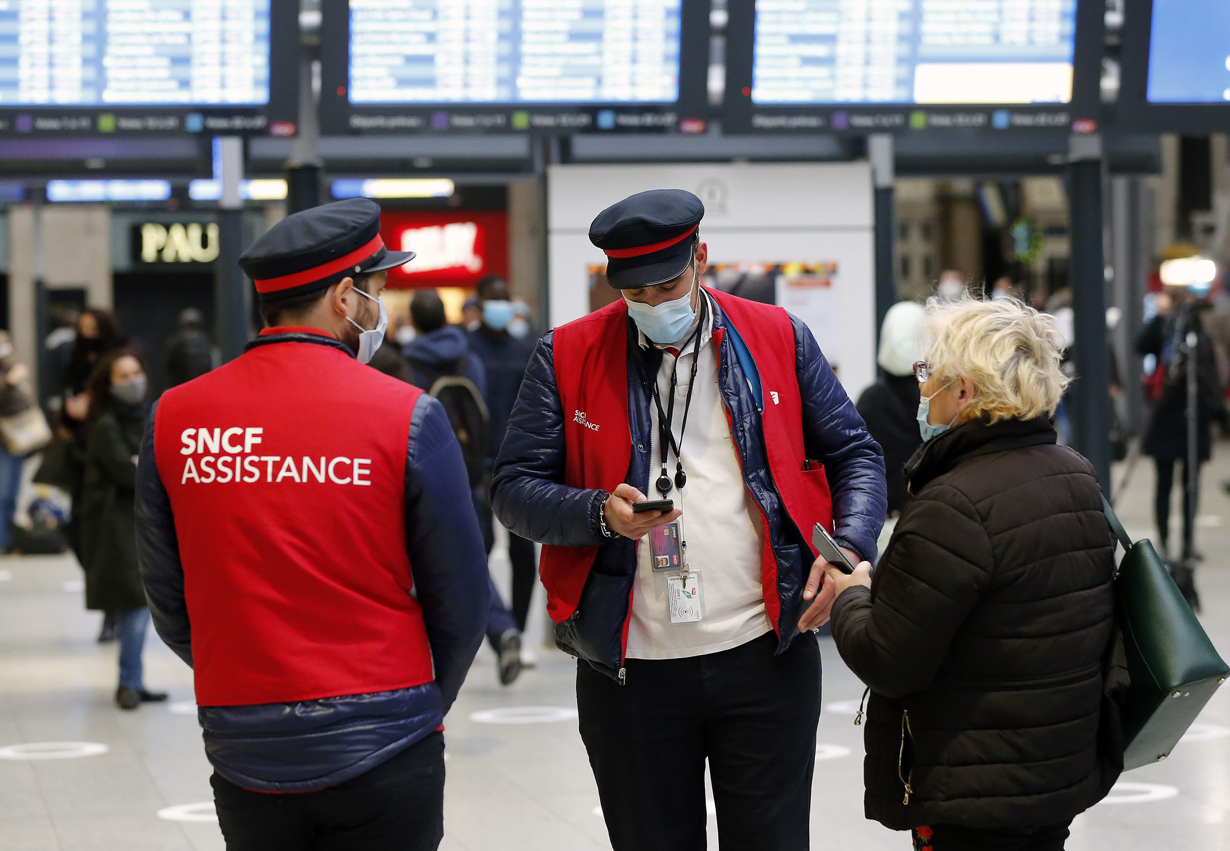 Rail company employees wear protective face masks at the Gare Saint Lazare railway station in Paris on Monday.