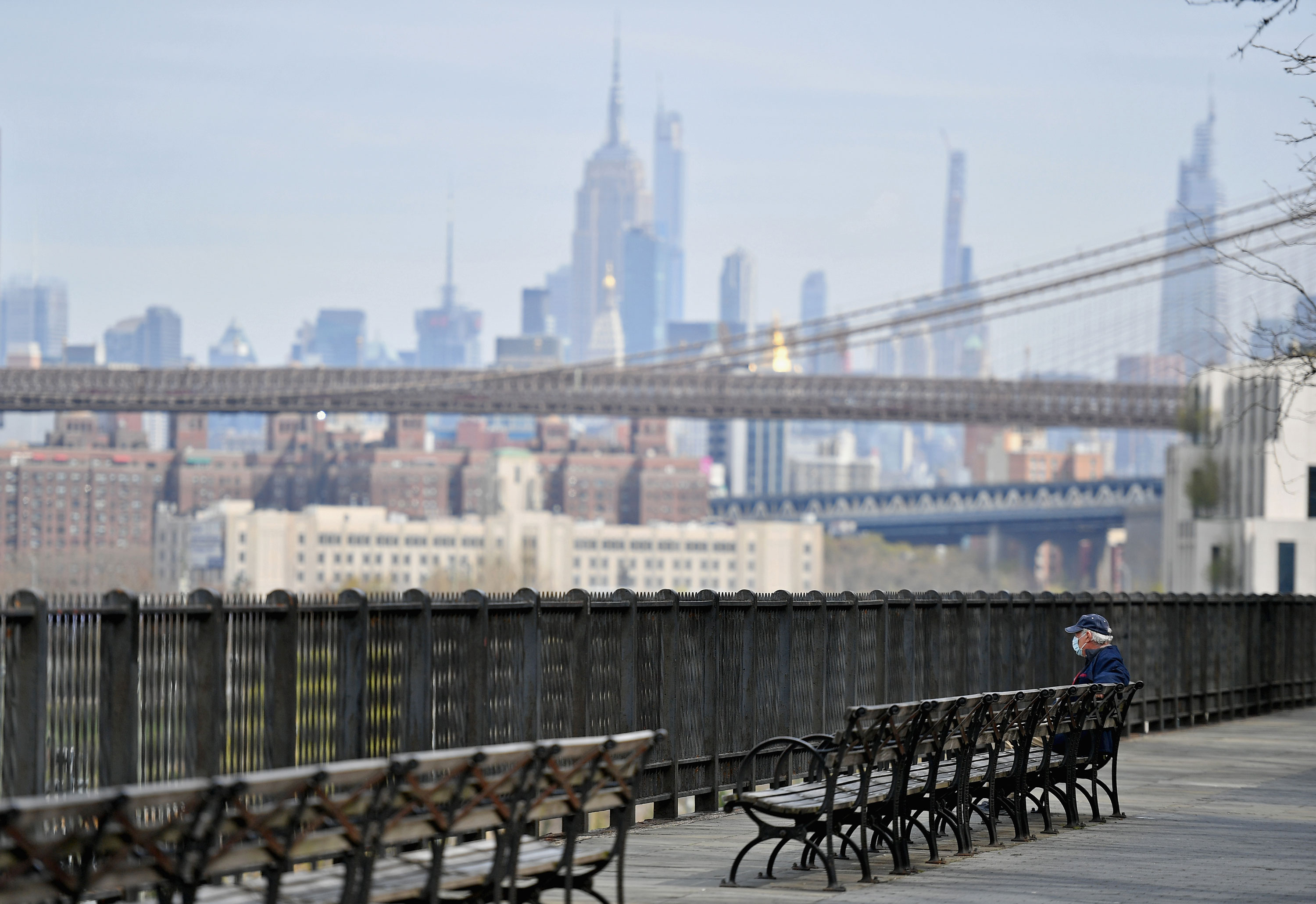 A man sits alone on a bench overlooking part of the Manhattan skyline amid the coronavirus pandemic on April 21 in Brooklyn, New York.