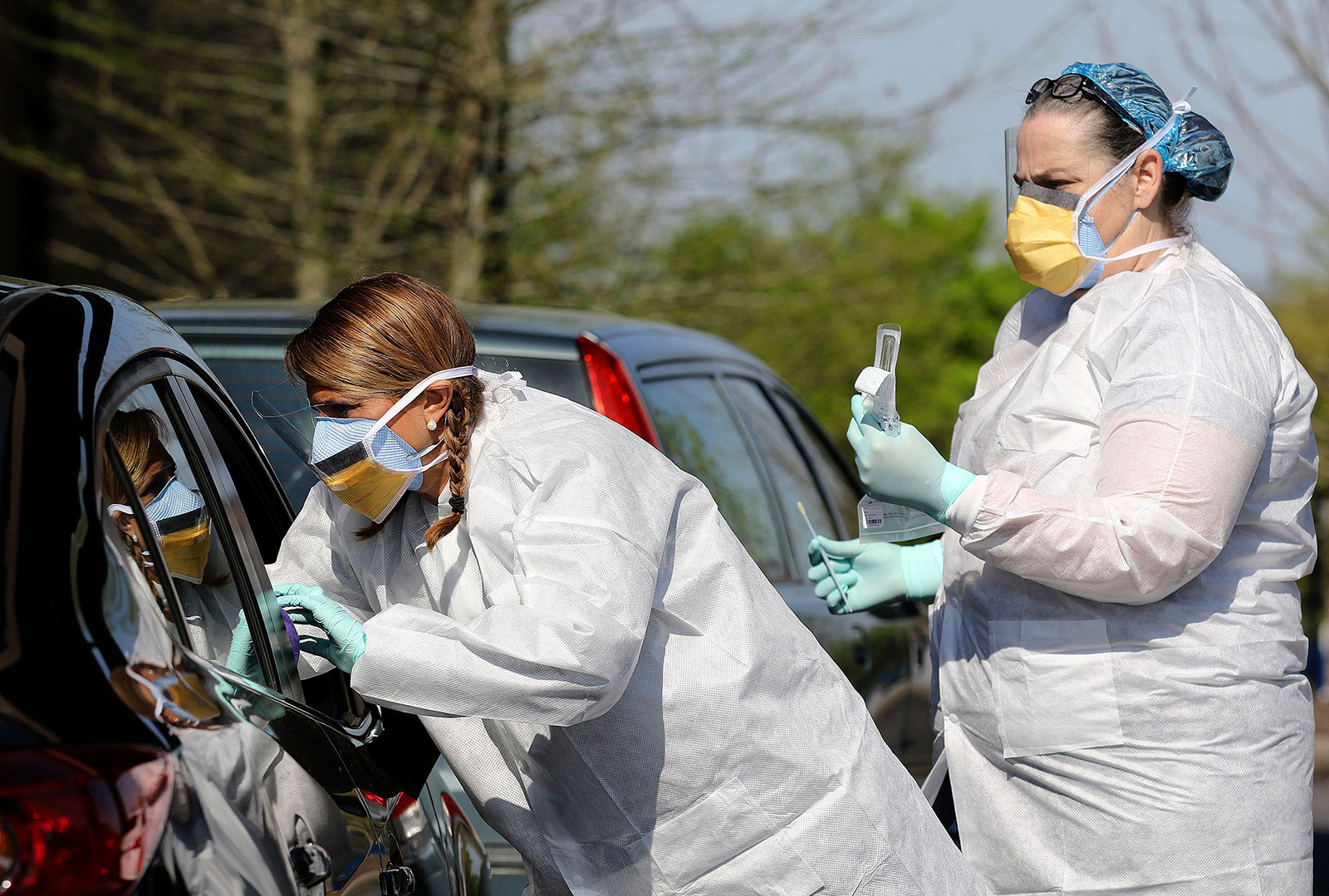 Nurse Mandy Stuckey reaches into a vehicle to administer a coronavirus test at a drive-through testing center in North Little Rock, Arkansas.