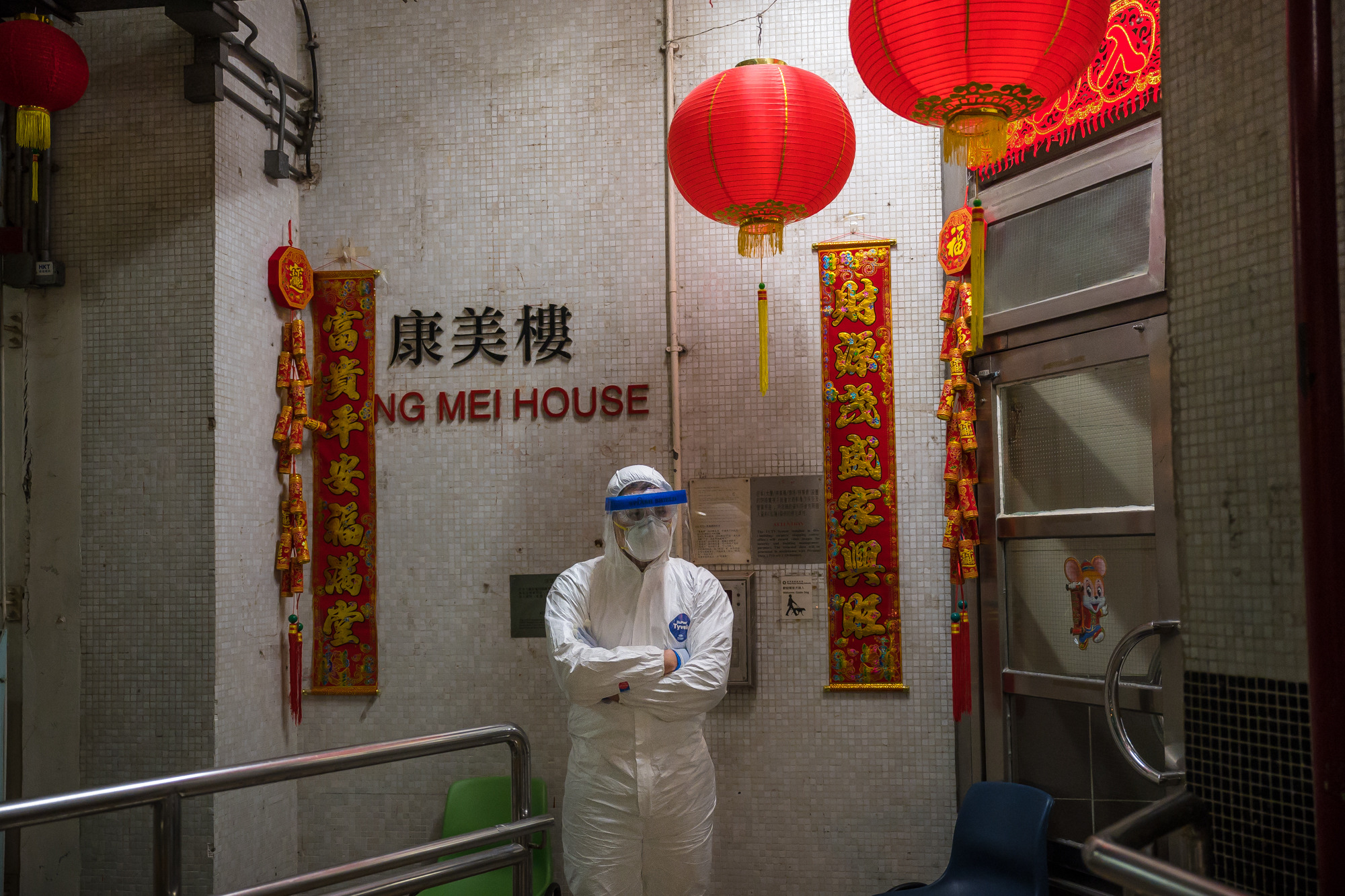 An official wearing protective gear stands guard outside an entrance to the Hong Mei House residential building at Cheung Hong Estate in Hong Kong's Tsing Yi district on Tuesday.