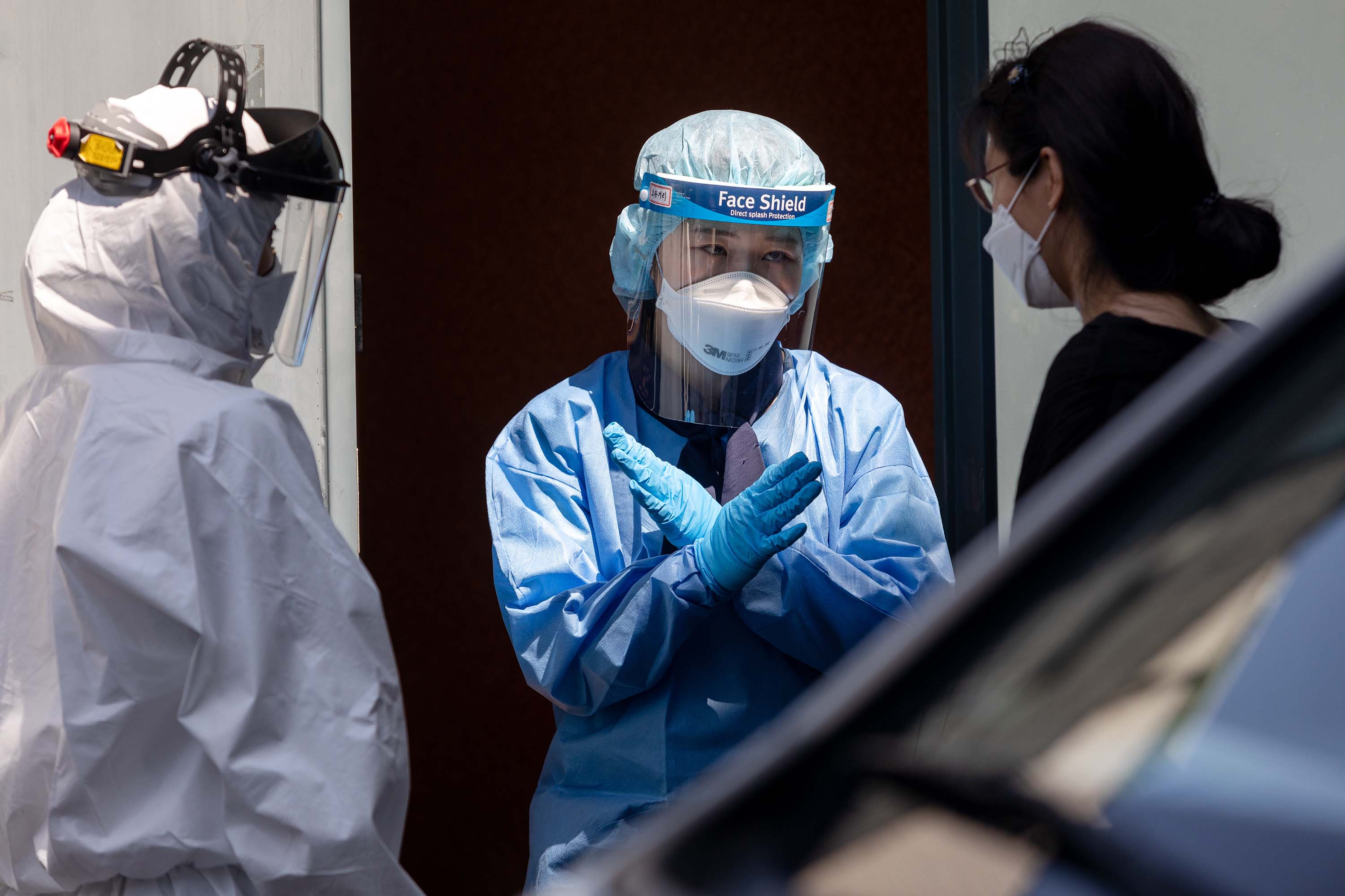 Medical workers speak with a person at a temporary coronavirus testing station in Seoul, South Korea, on June 11.