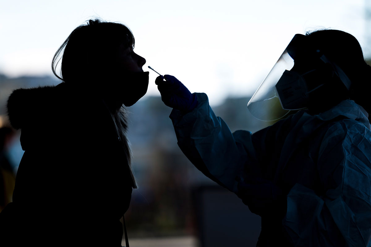 A medical worker wearing personal protective equipment administers a Covid-19 test at the Alemany Farmers Market in San Francisco, California, on November 19.