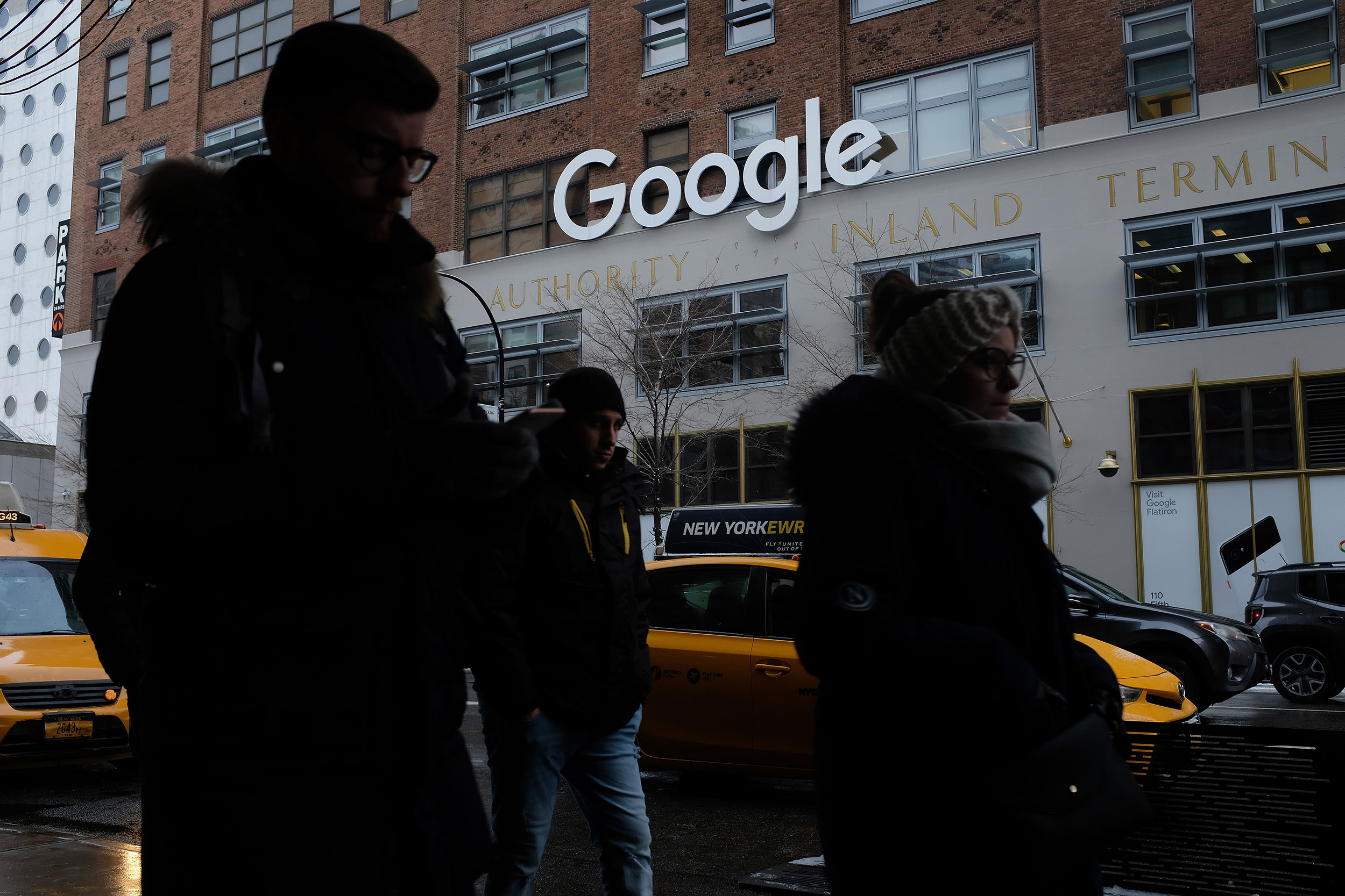 People walk past the Google office building in New York City on December 30, 2017.
