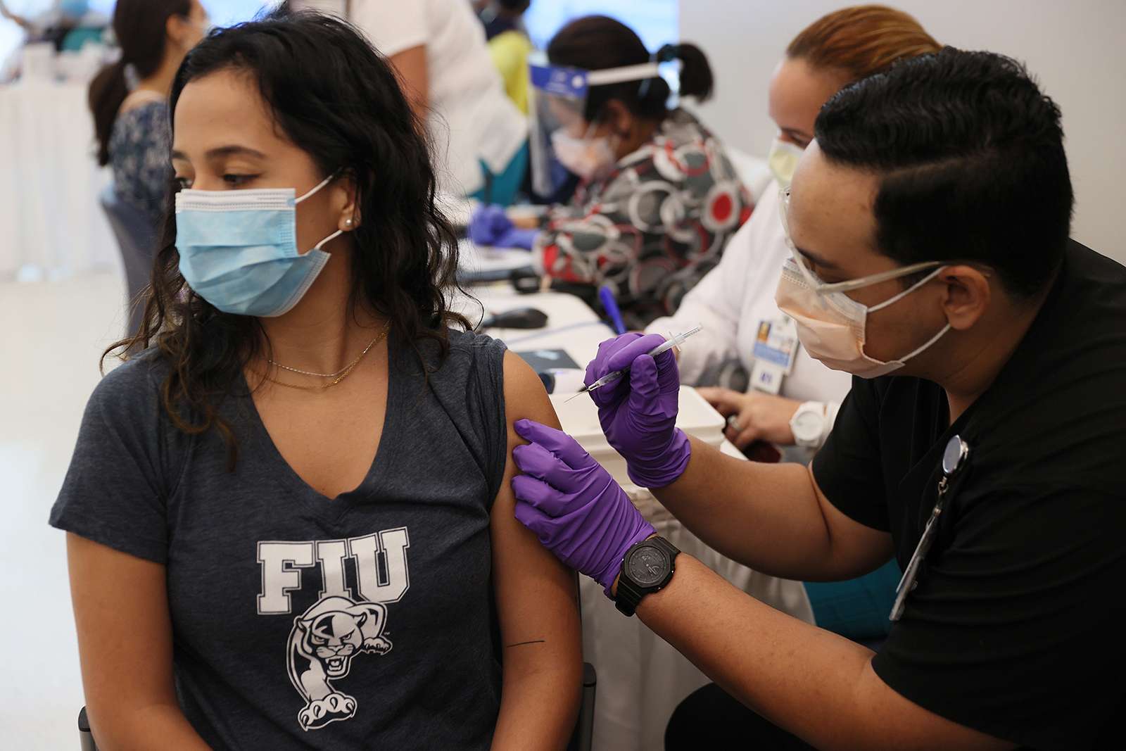 Camila Gutierrez, a junior at Florida International University, receives a Pfizer-BioNtech Covid-19 vaccine from Jason Rodriguez, a pharmacy student, at the Jackson Memorial Hospital on April 15, in Miami.