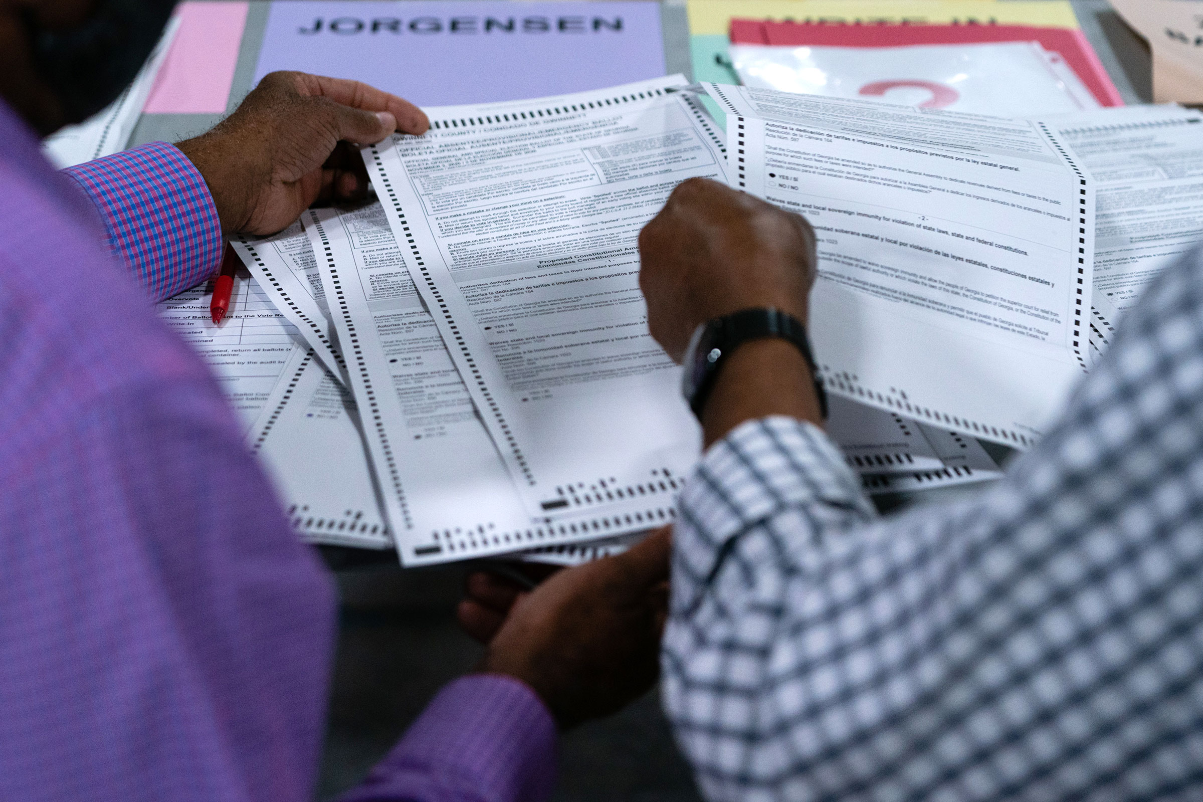 People hand count ballots at the Gwinnett County Voter Registration office on November 13 in Lawrenceville, Georgia