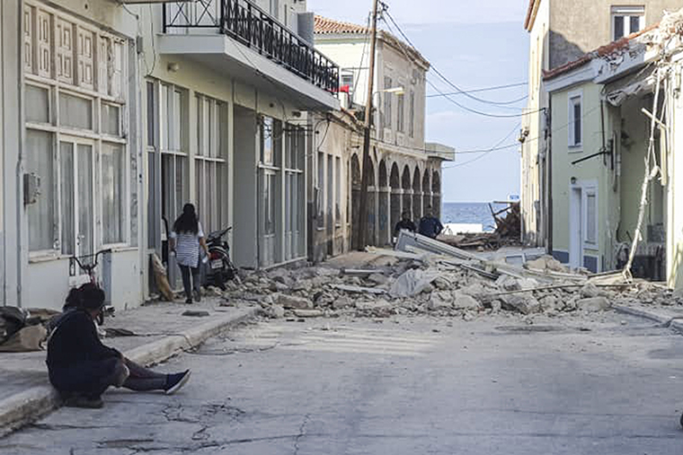 People walk past a destroyed house after an earthquake on the island of Samos on October 30, 2020