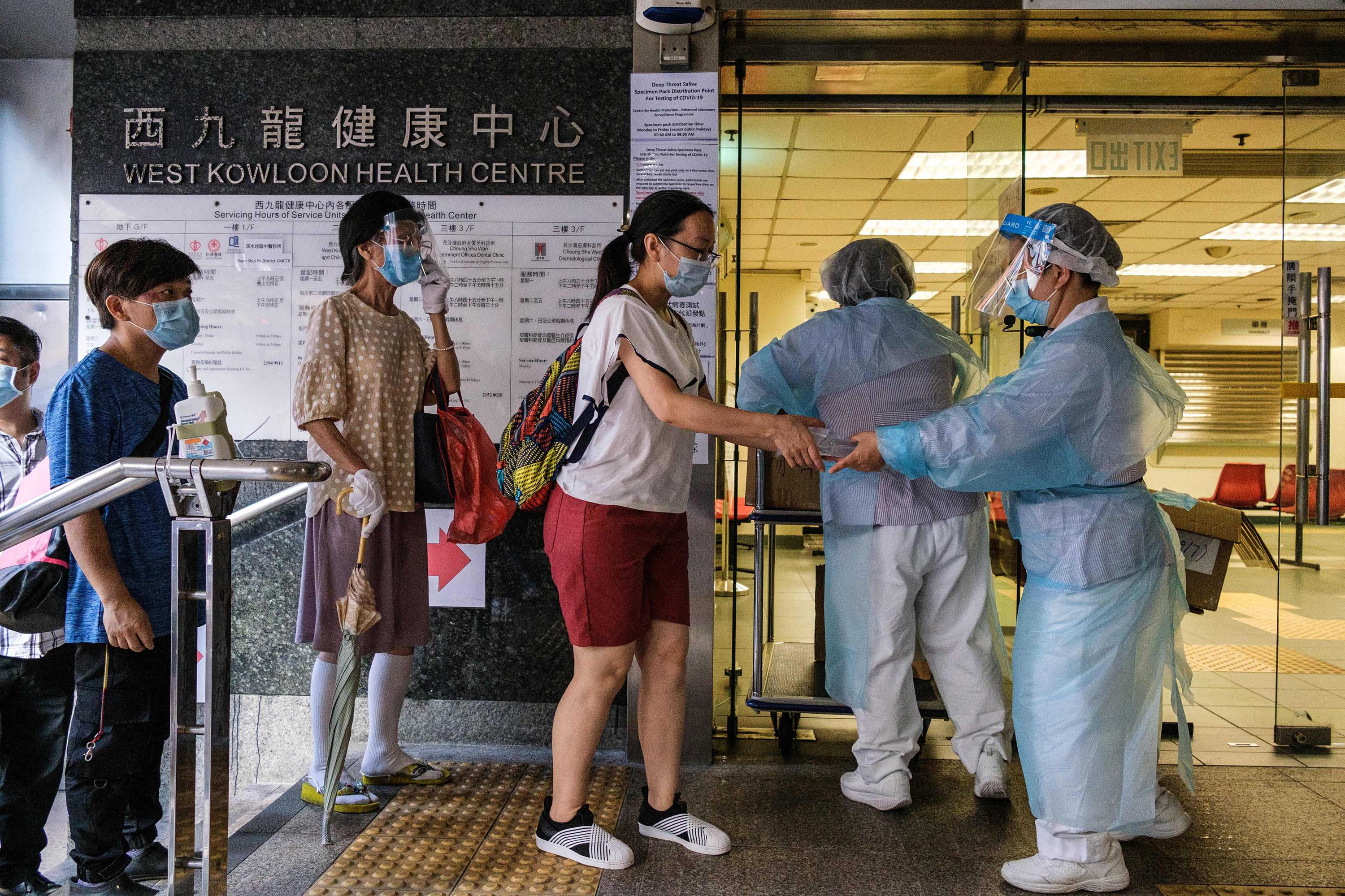 Residents are given free Covid-19 test kits by workers at a government clinic in Hong Kong on Wednesday, July 29, 2020, as part of a city-wide testing initiative.