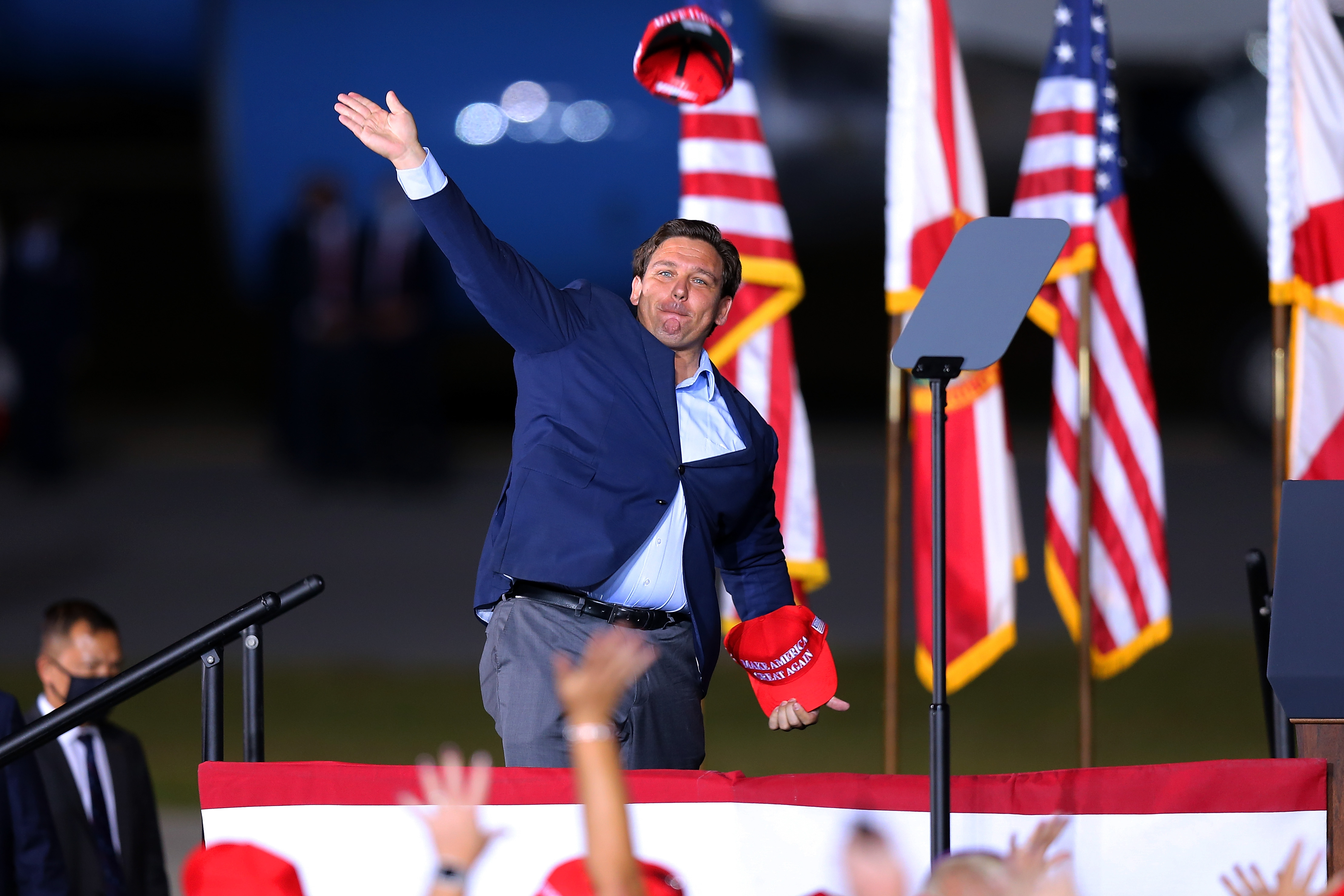 Florida Governor Ron DeSantis throws a hat to supporters during a rally for President Donald Trump on October 23, in Pensacola, Florida.