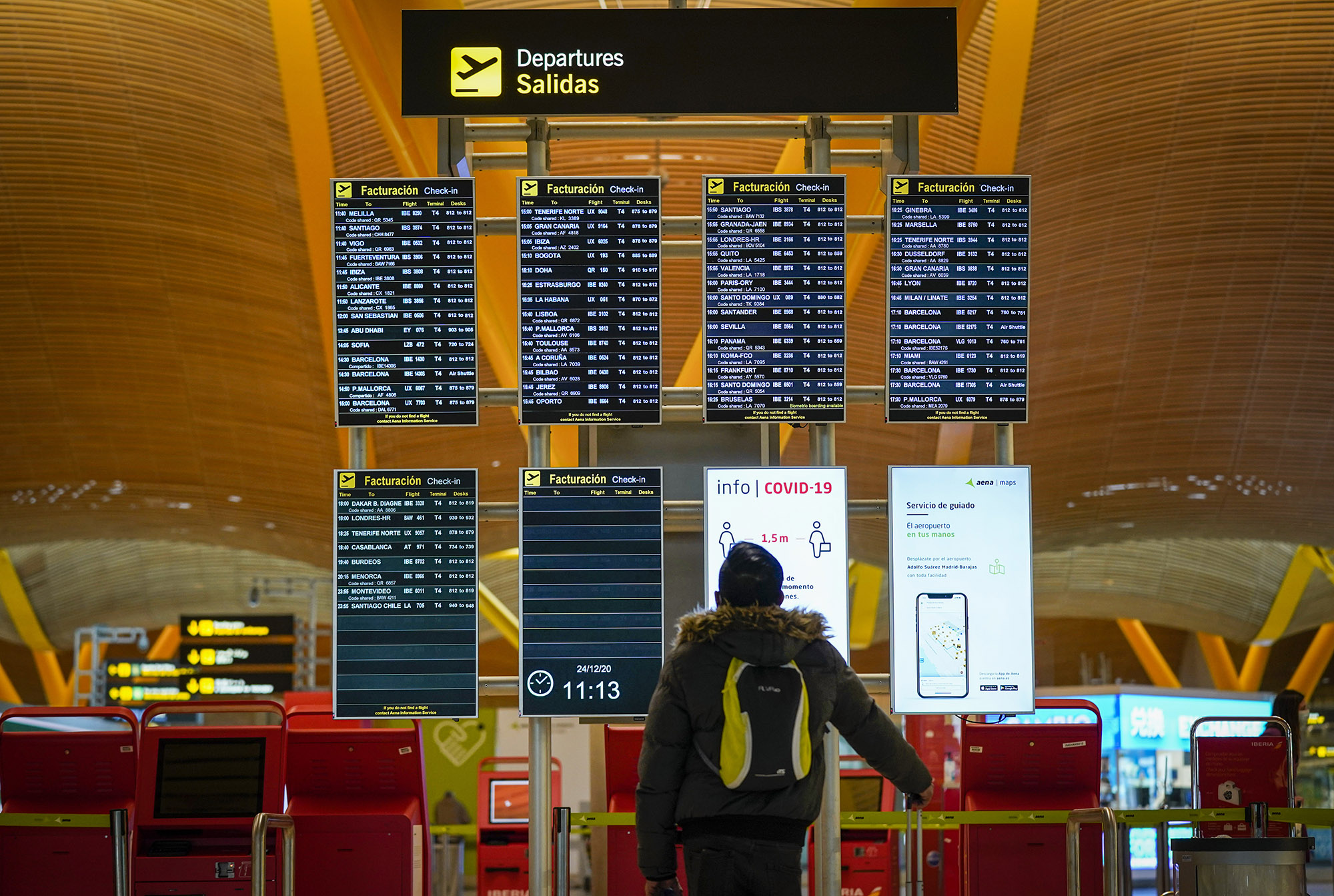 A passenger checks flight information on a board in the departures hall at Madrid Barajas airport, in Madrid, Spain, on Thursday, December 24.
