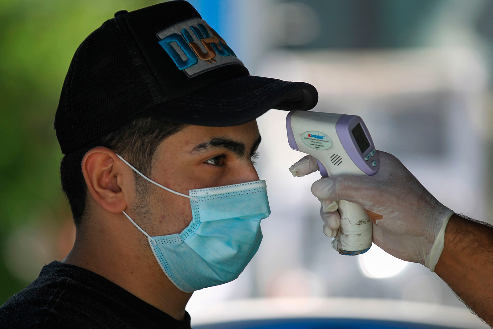 A customer has his temperature checked before entering a supermarket in the Iraqi capital Baghdad, on June 23.
