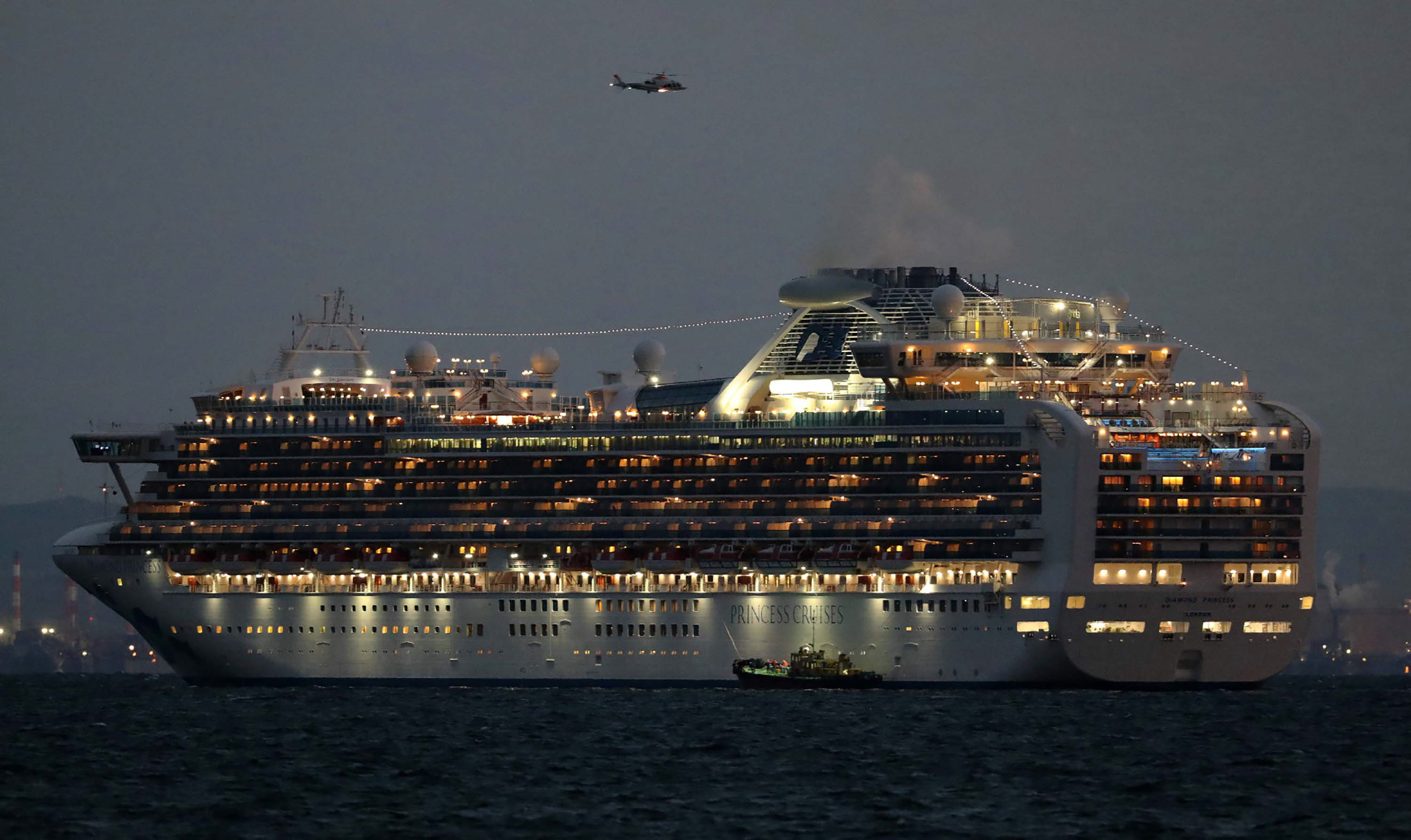 A small boat is pictured next to the Diamond Princess cruise ship with over 3,000 people as it sits anchored in quarantine off the port of Yokohama on February 4.