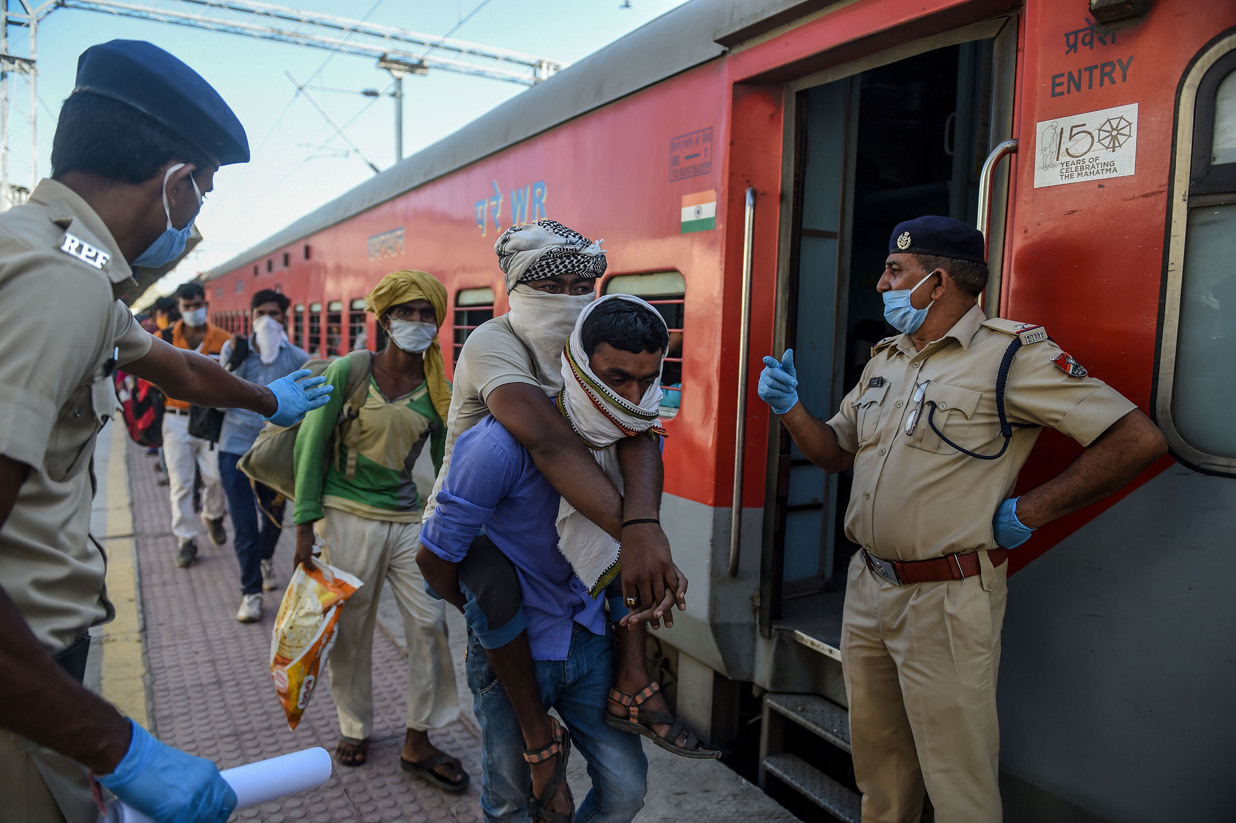 A migrant worker lifts his disabled brother, center, as they board a special train at Sabarmati Railway Station near Ahmedabad, India, on May 2.