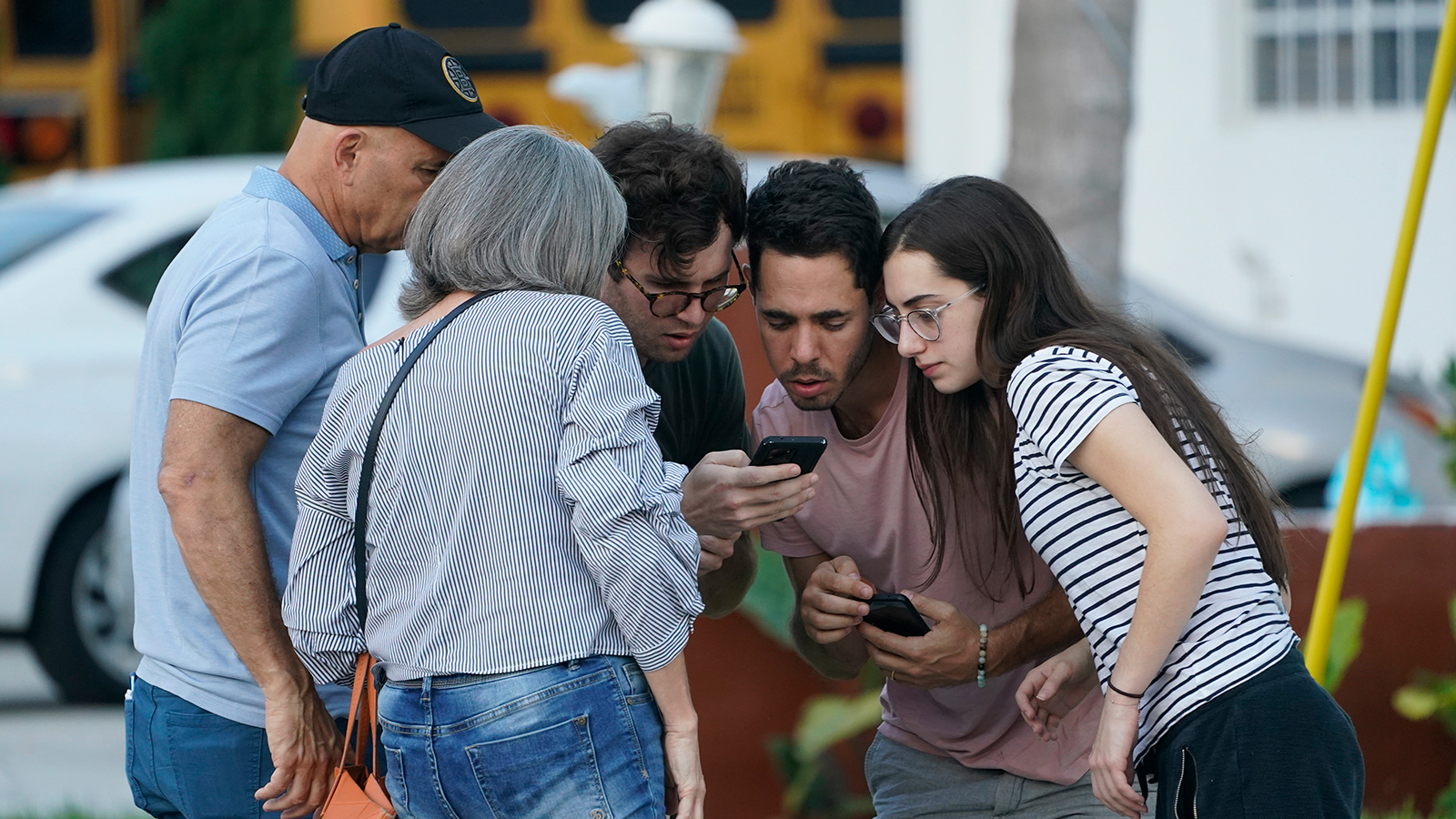 People wait for information after a partial building collapse on Thursday, June 24, in Surfside, Florida.