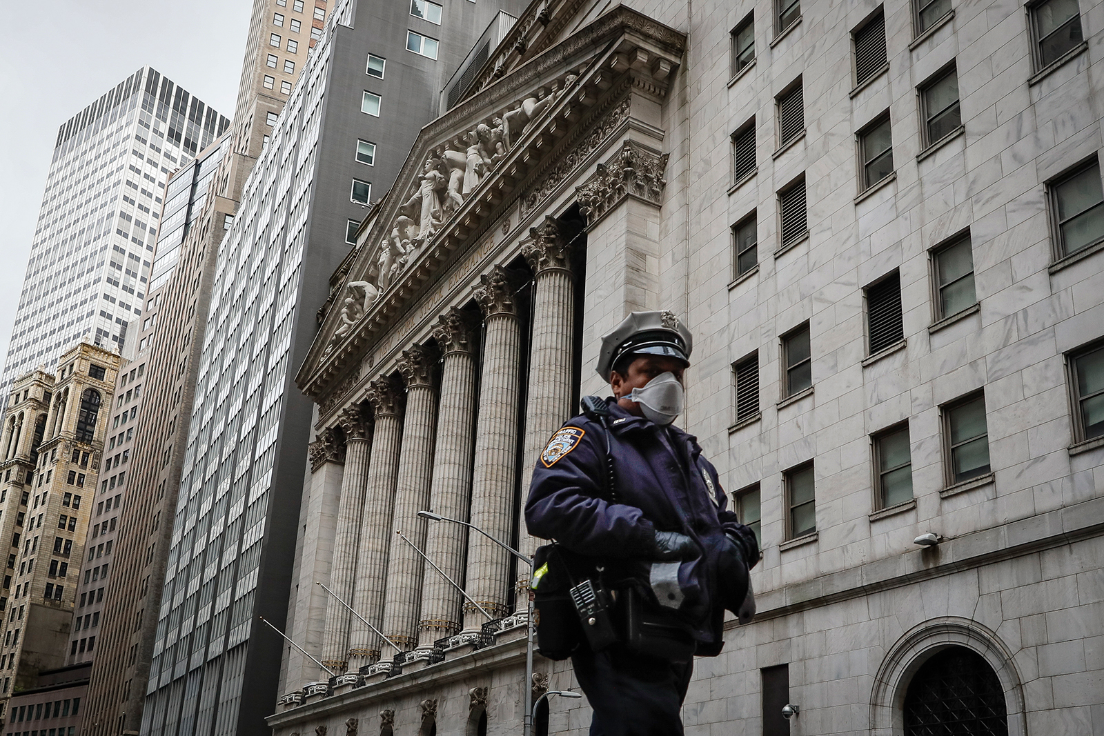 An NYPD officer walks along a sparsely populated Wall Street in New York City, NY on May 1.