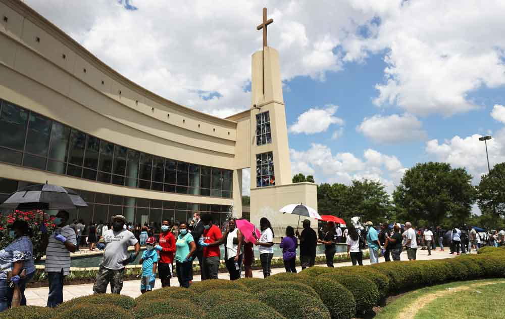 People wait to attend the public memorial for George Floyd outside of the Fountain of Praise church on Monday in Houston, Texas.