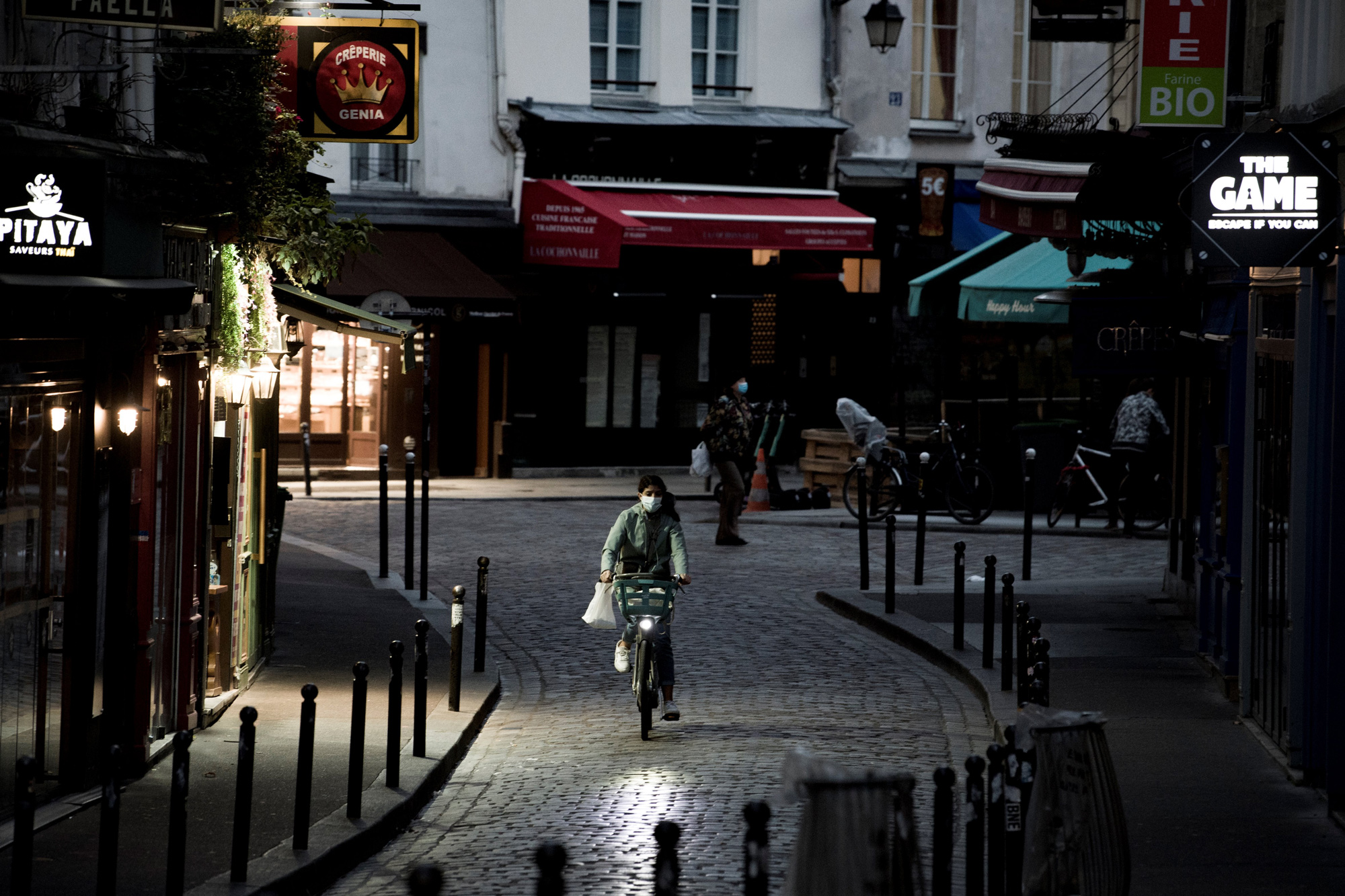 A woman rides her bike in the district of St Michel on November 3 in Paris.