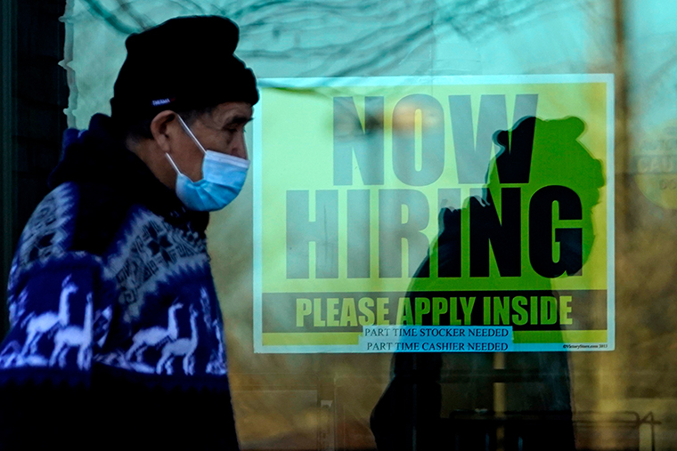 A shopper wears a face mask and he walks past a store displaying a hiring sign in Wheeling, Ill., Saturday, Nov. 28, 2020.