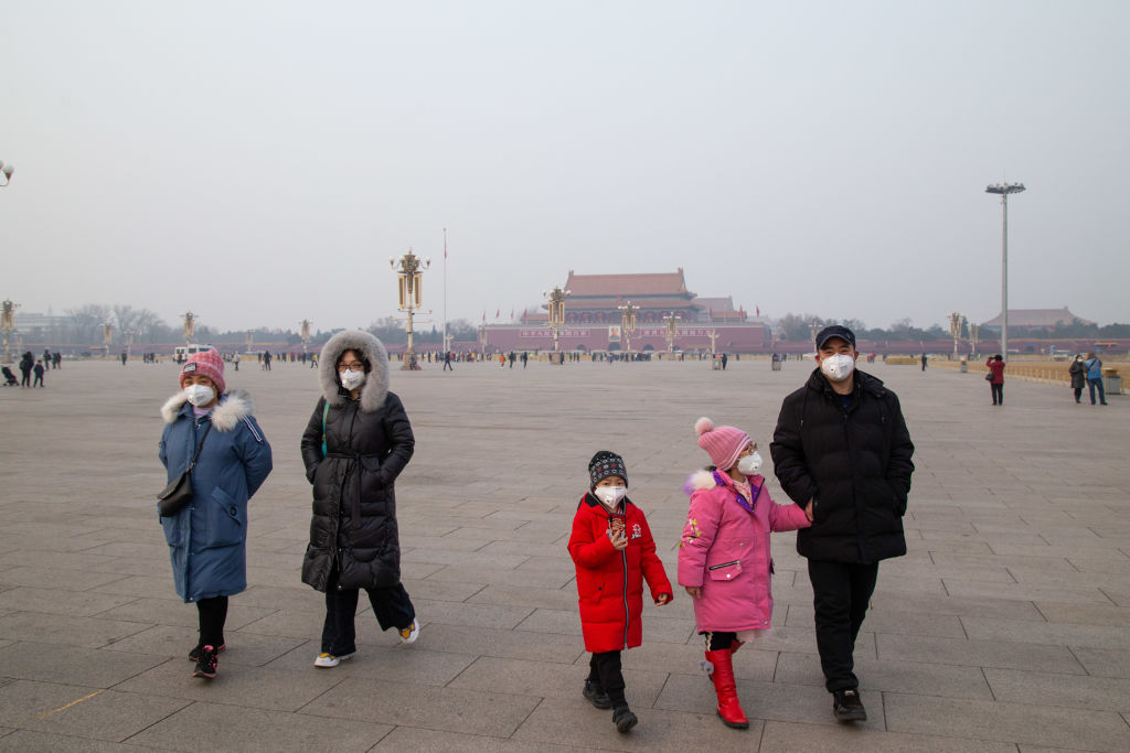 A family wearing masks are seen in Tiananmen Square on January 26, 2020 in Beijing, China.