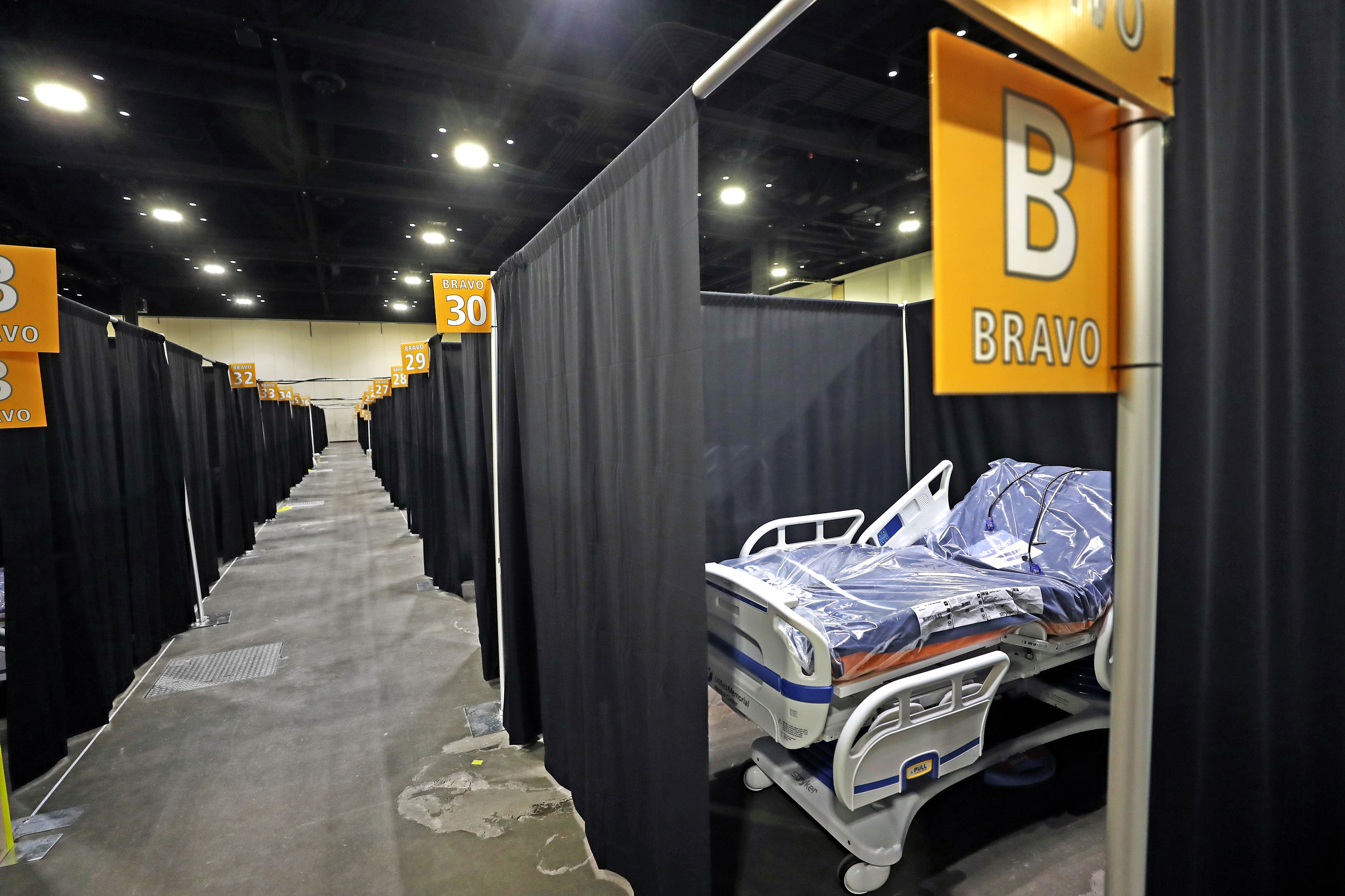 Individual hospital beds are lined up in a corridor with curtains at the new temporary hospital at the DCU in Worcester, MA on November 25. The hospital is being set up for a second time within a year.