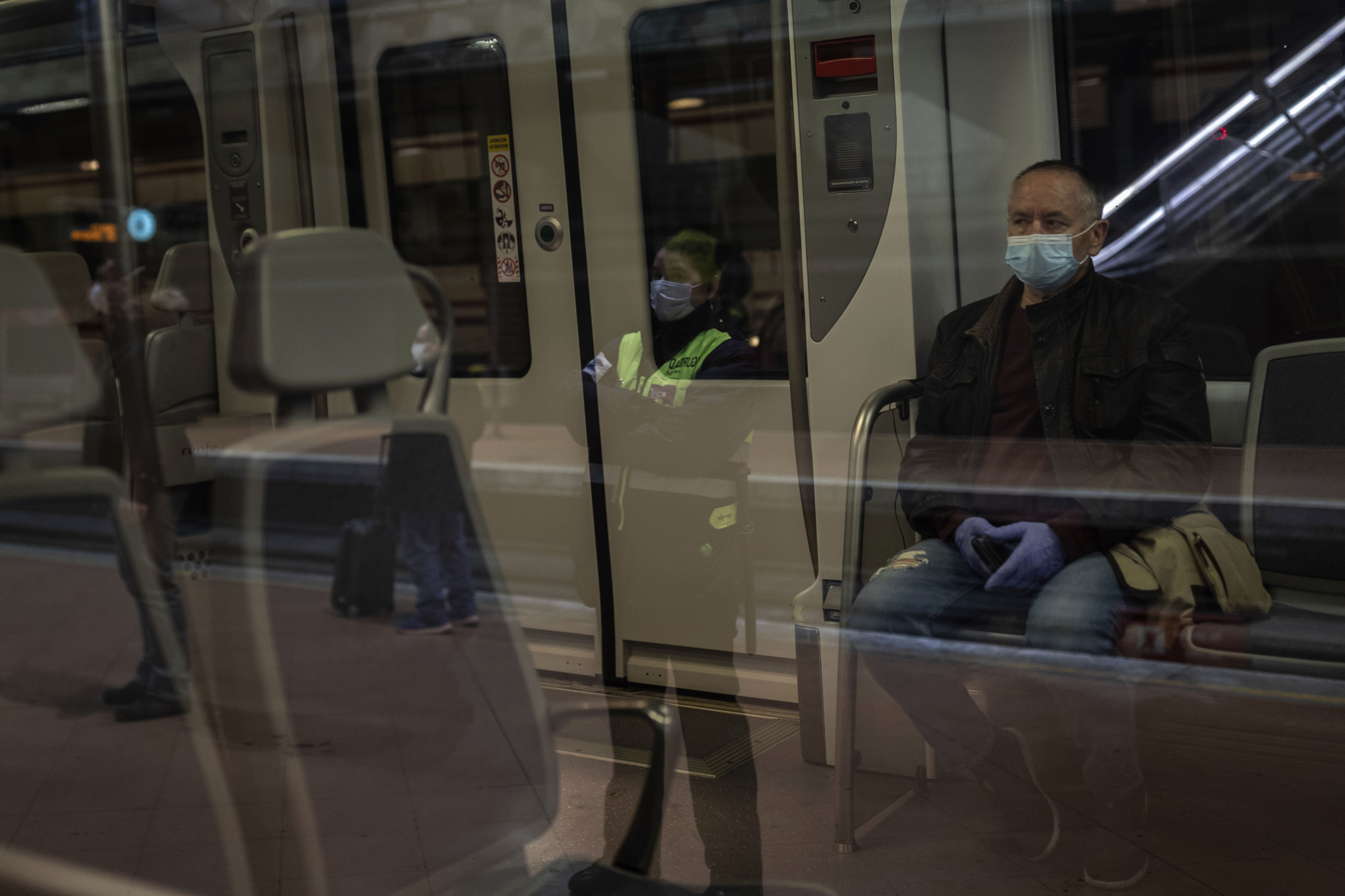 Commuters wear face masks at Atocha train station in Madrid on April 13.