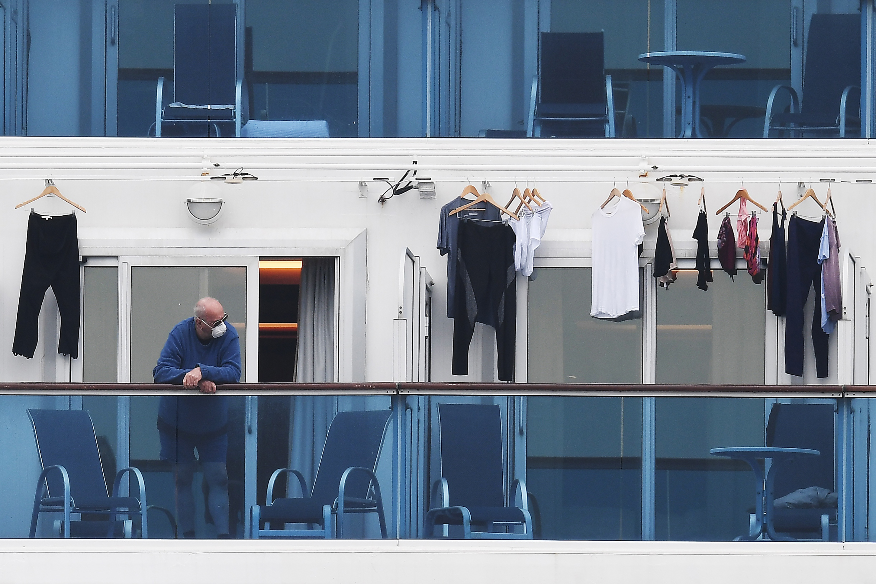 A passenger is seen on a balcony of the Diamond Princess cruise ship.
