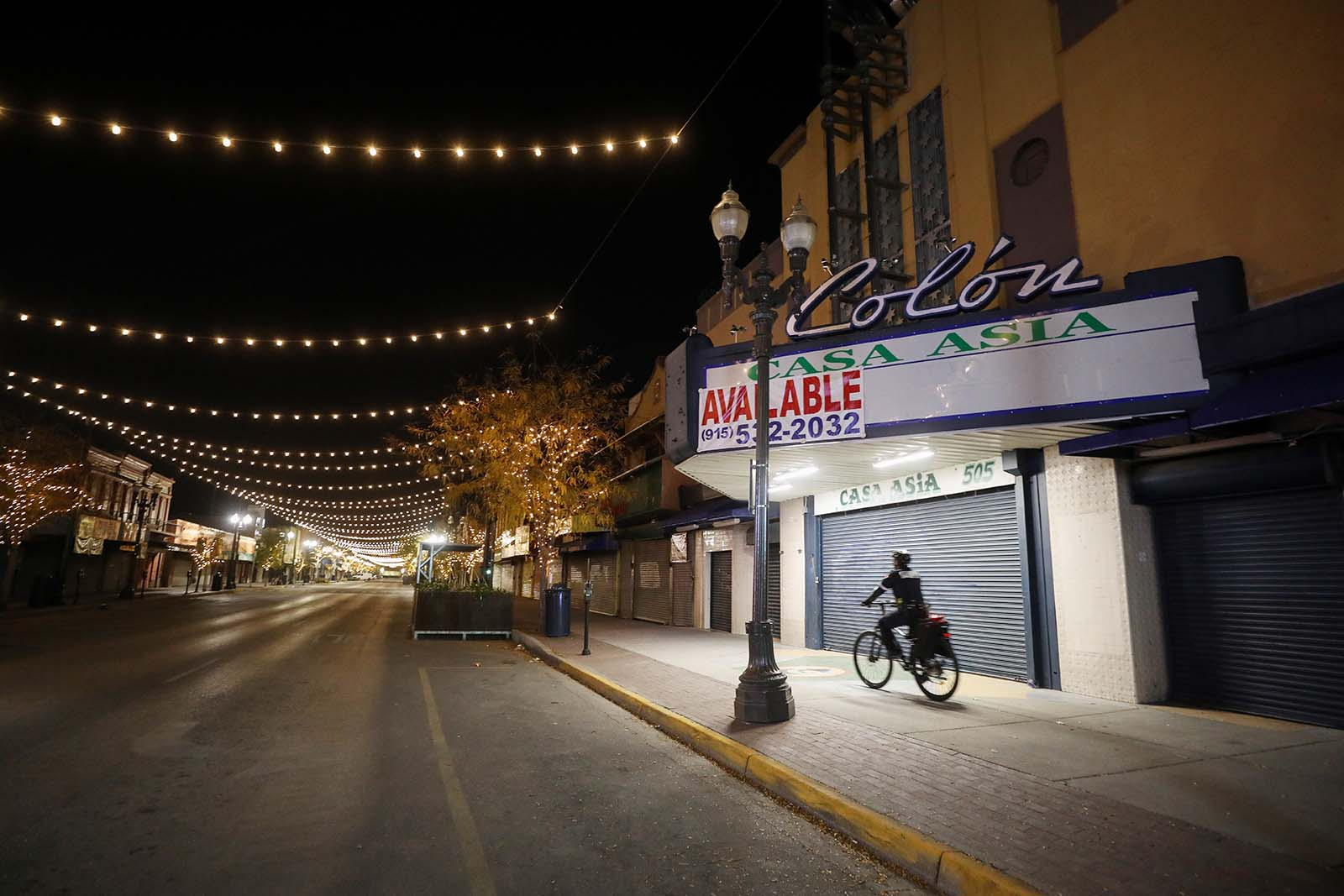 A police officer on a bike patrols an empty downtown street amid a surge of coronavirus cases on November 12, in El Paso, Texas.