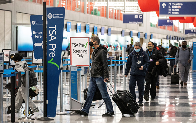 Travelers wearing face masks line up for security checks at O'Hare International Airport in Chicago on Nov. 25, 2020.