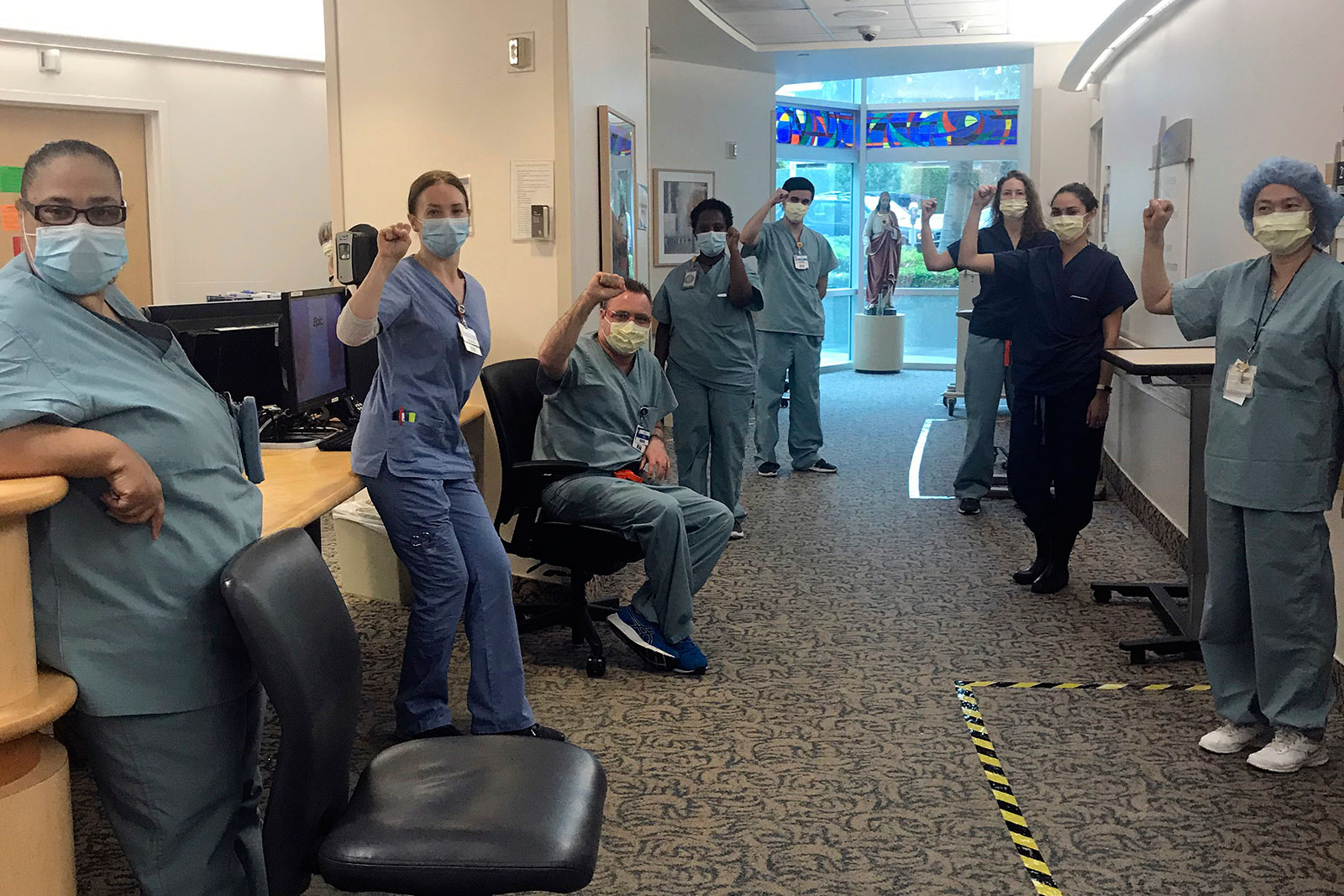 Nurses raise their fists in solidarity after telling managers they won't care for Covid-19 patients without N95 respirator masks to protect themselves at Providence Saint John's Health Center in Santa Monica, California, on April 10.