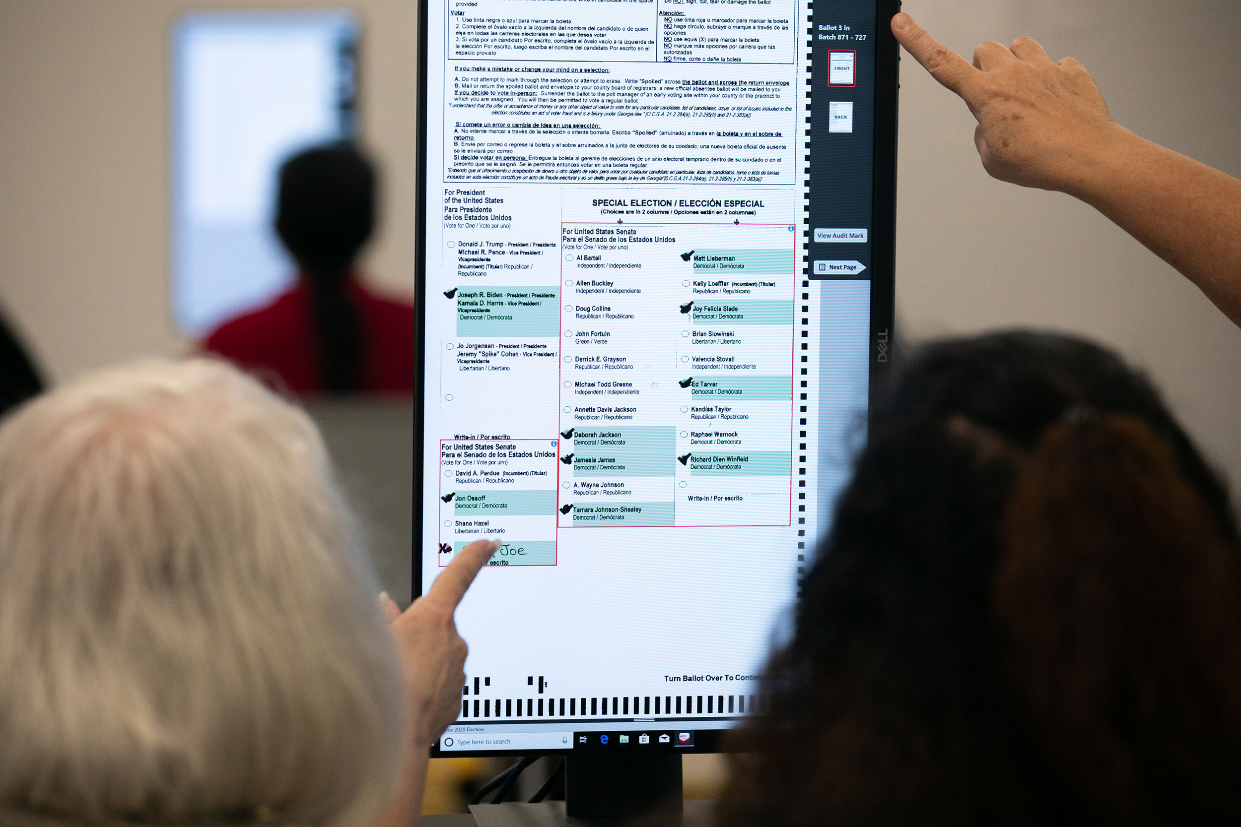Members of the Gwinnett County adjudication review panel look over ballots on November 8 in Lawrenceville, Georgia.