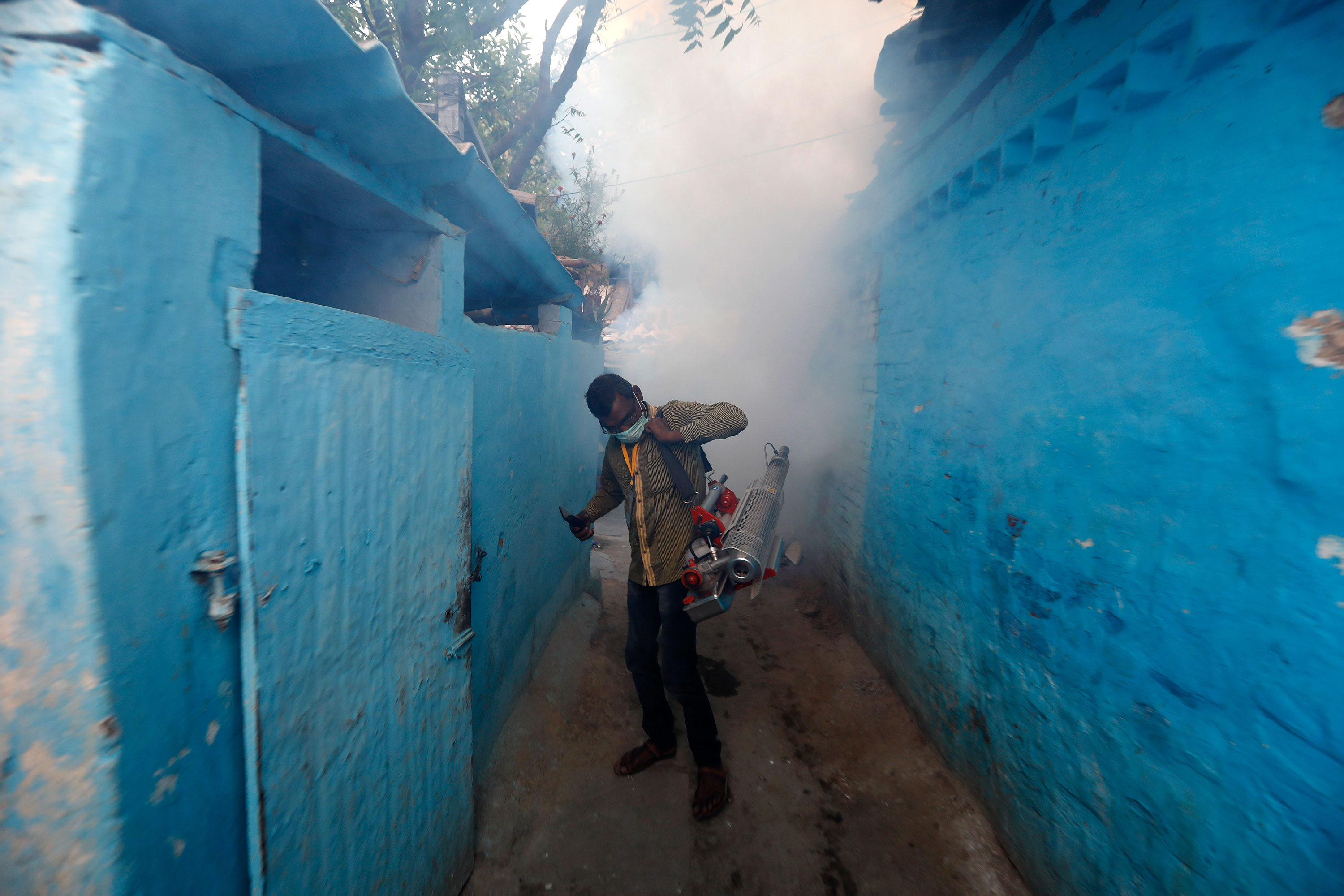 A municipal worker fumigates a residential area in Prayagraj, India, on April 4.