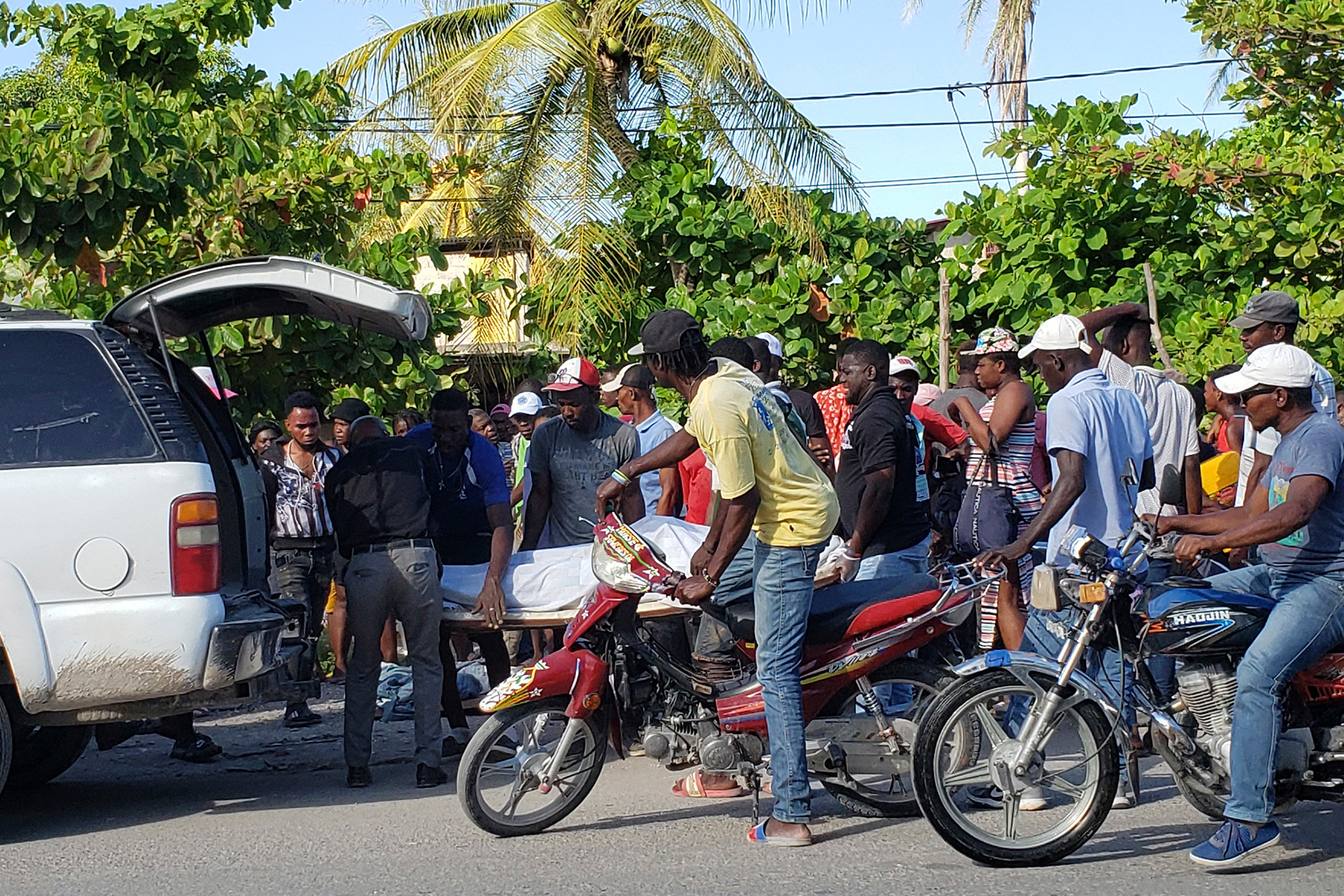 People watch an earthquake victim be placed into a vehicle in Les Cayes, Haiti, on August 14.