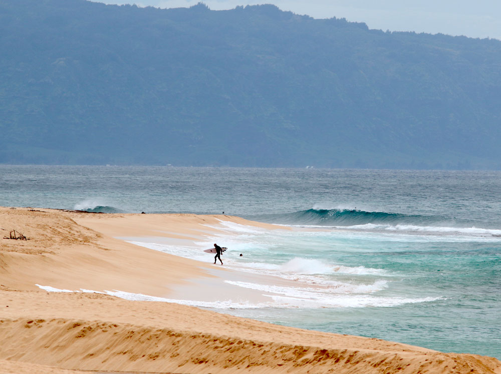 A surfer walks out of the ocean on Oahu's North Shore near Haleiwa, Hawaii, on Tuesday, March 31.