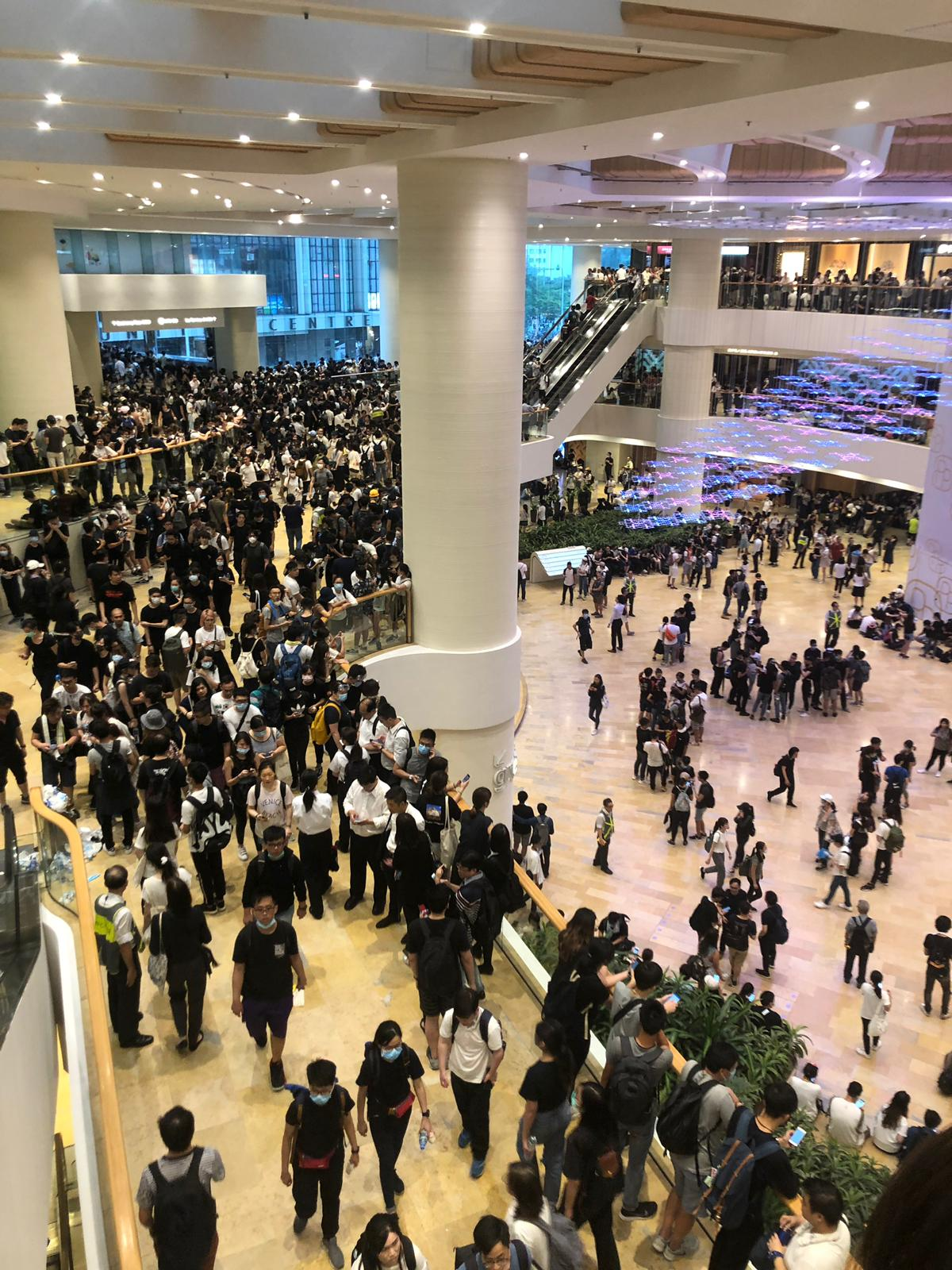 The Pacific Place mall is packed with young protestors, many wearing black shirts and face masks.