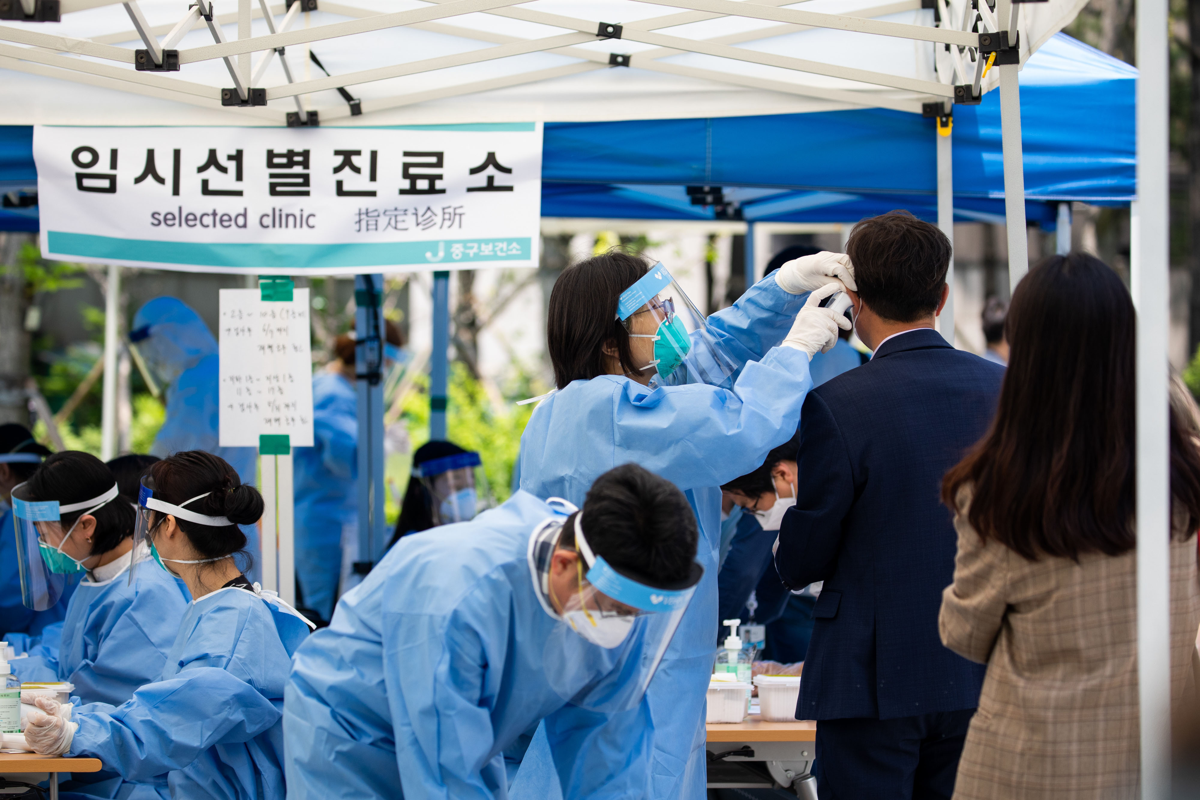 A medical worker checks the temperature of a man at a temporary coronavirus testing station in Seoul, South Korea, on May 29.