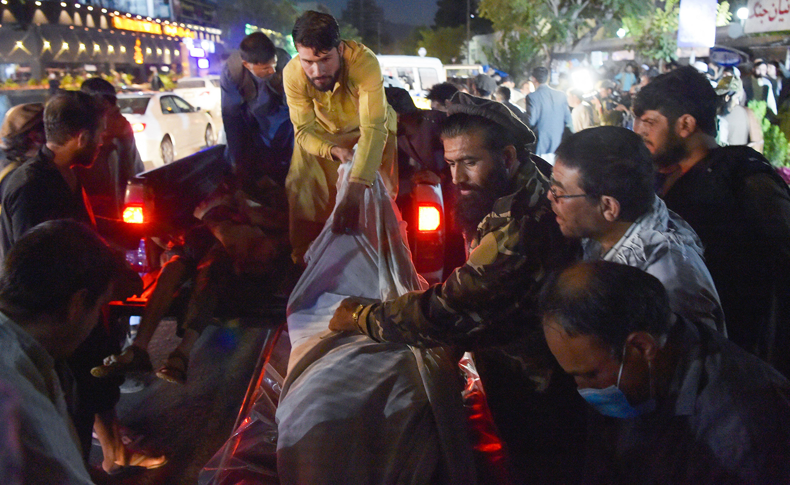 Volunteers and medical staff unload bodies from a pickup truck outside a hospital after explosions in Kabul on August 26.