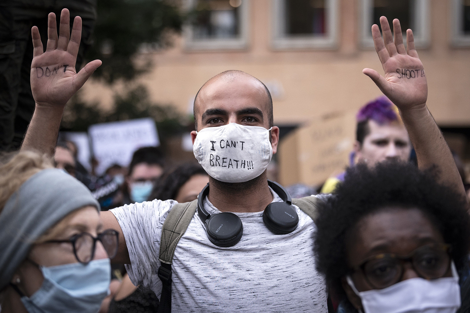 A demonstrator holds up his hands with the lettering 'Don't shoot' and wears a face mask with the lettering 'I can't breathe' in Toulouse, southern France, on June 3.