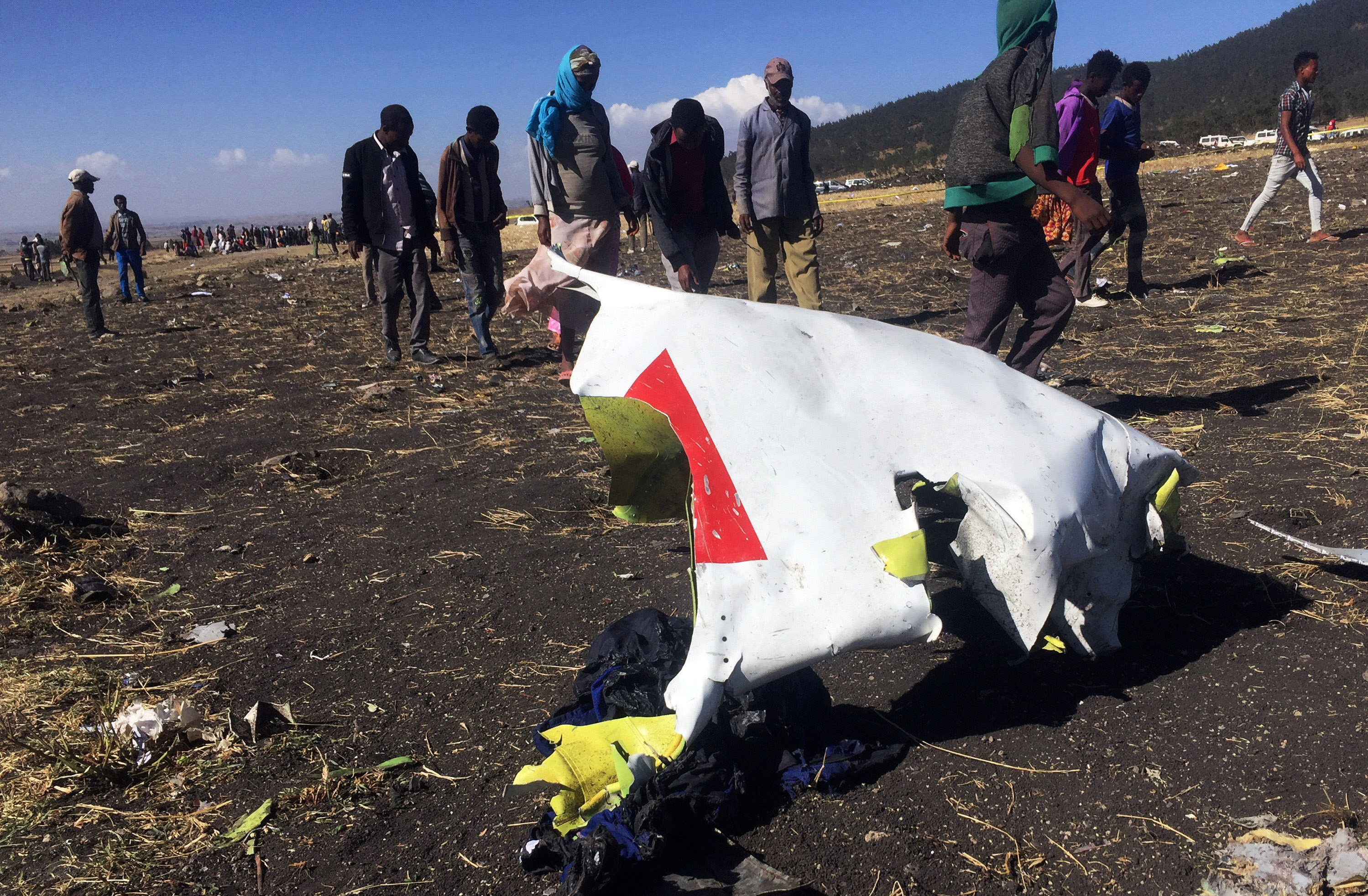 People walk past a part of the wreckage at the scene of the Ethiopian Airlines Flight ET 302 plane crash, near the town of Bishoftu, southeast of Addis Ababa, Ethiopia on March 10, 2019.