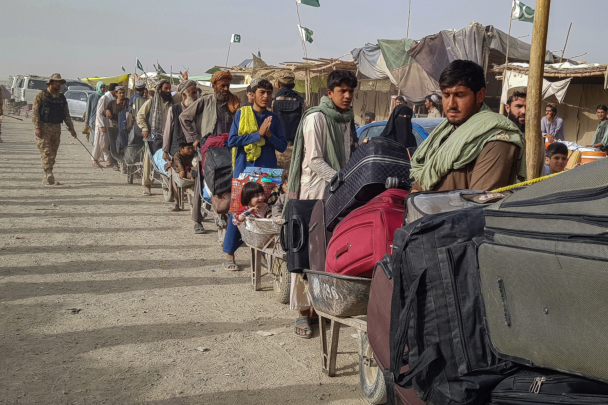 Afghan nationals queue up at the Pakistan-Afghanistan border crossing point in Chaman, on August 17.