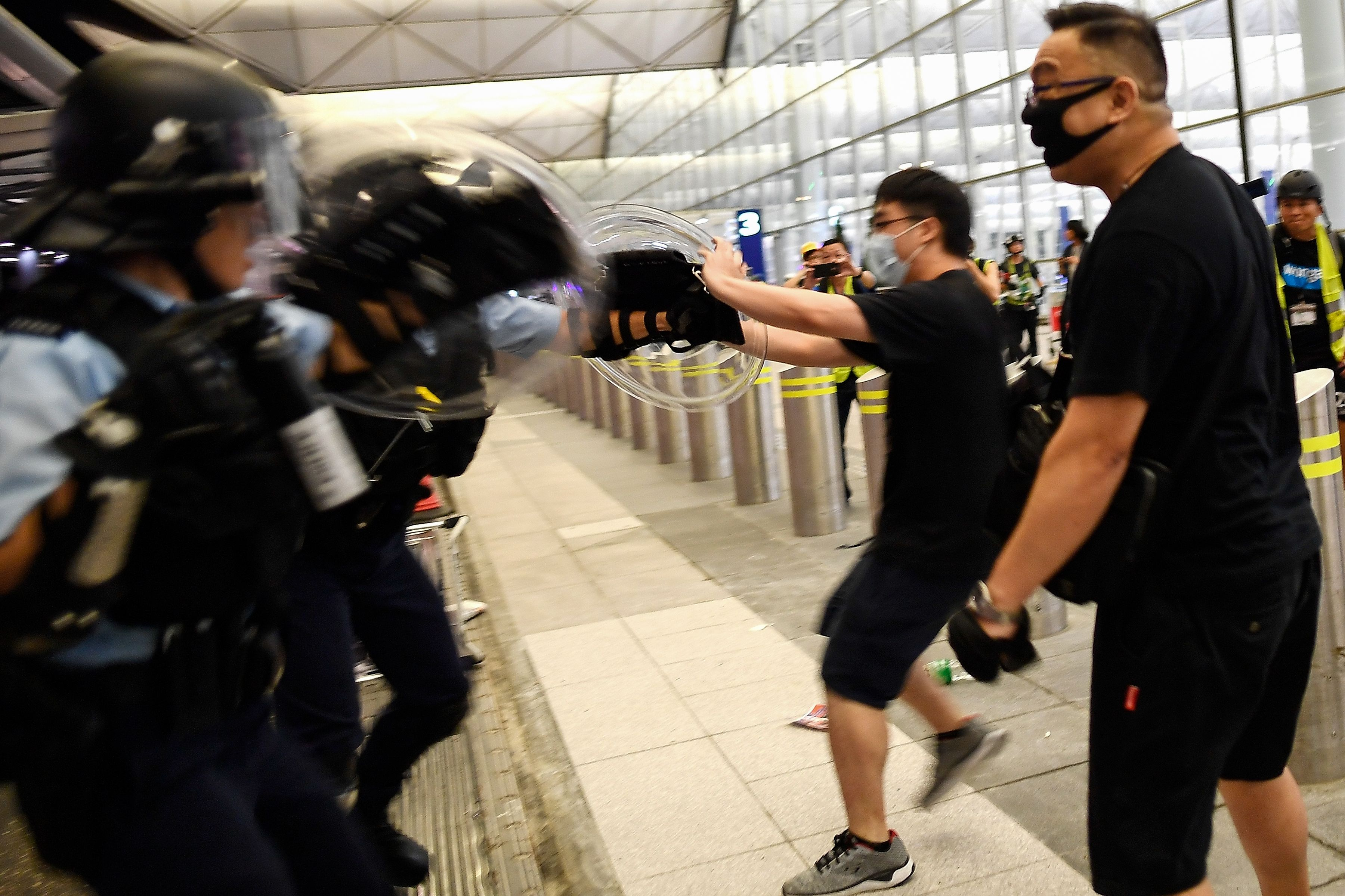 Police scuffle with pro-democracy protestors at Hong Kong International Airport on August 13, 2019.
