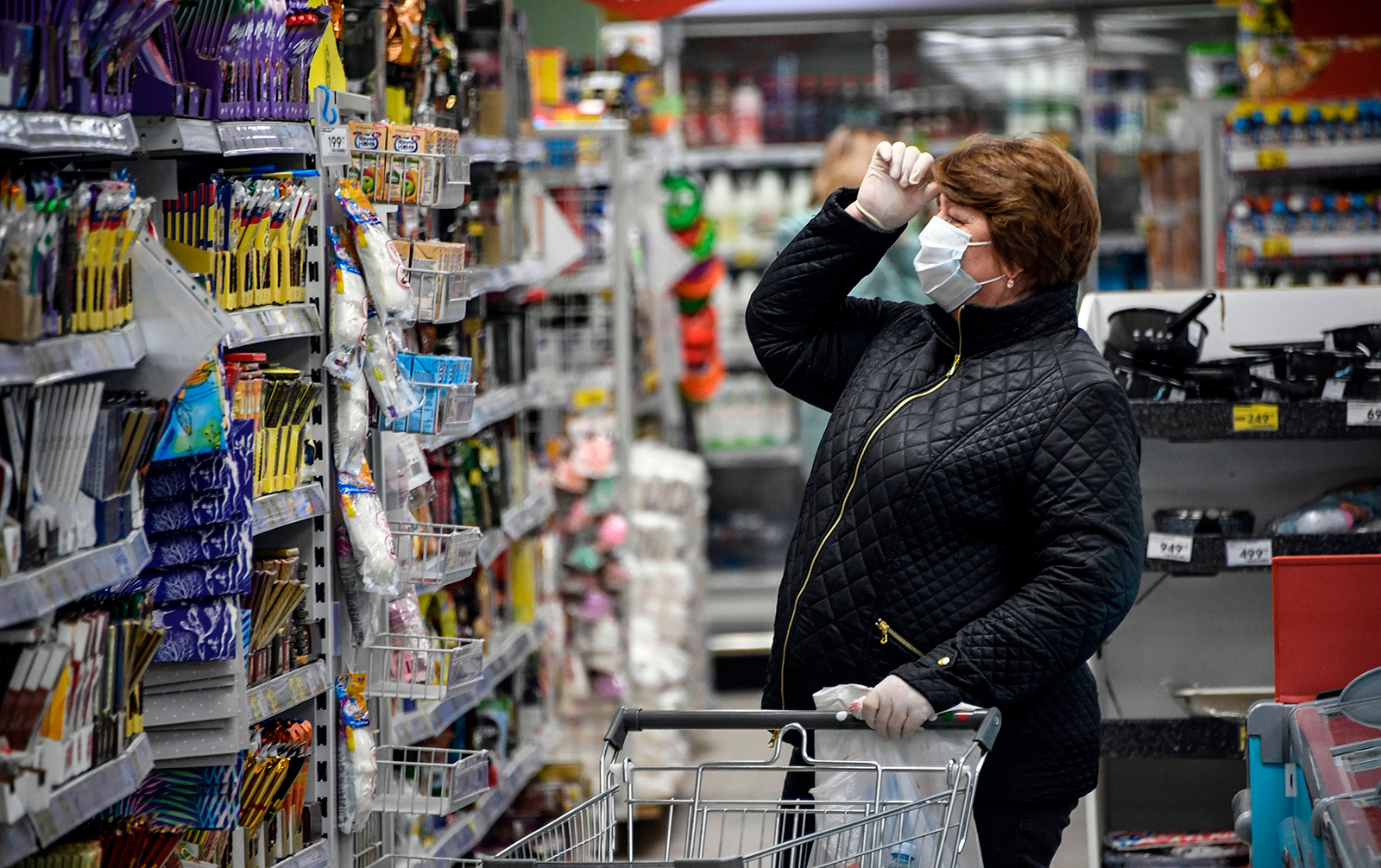 A woman wears a protective mask and gloves while shopping in a supermarket in Moscow on Wednesday.