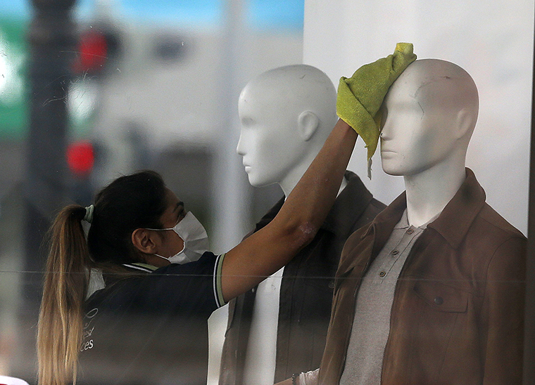 A person wearing a face mask cleans mannequins of a store in Ankara, Turkey on Monday, May 4, after Turkey lifted a 72-hour coronavirus restrictions as of midnight Sunday.