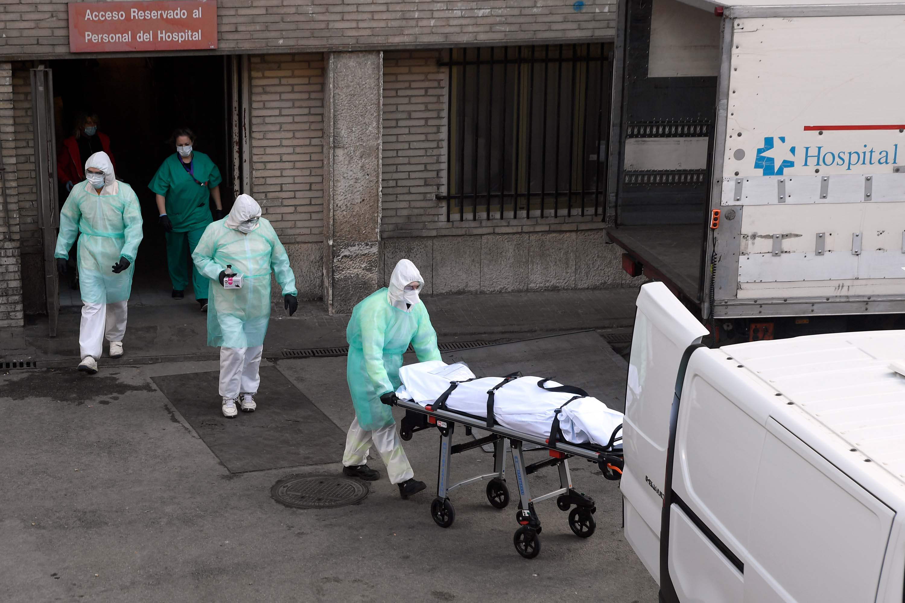 Health workers transport a body on a stretcher outside the Gregorio Maranon hospital in Madrid on March 25.